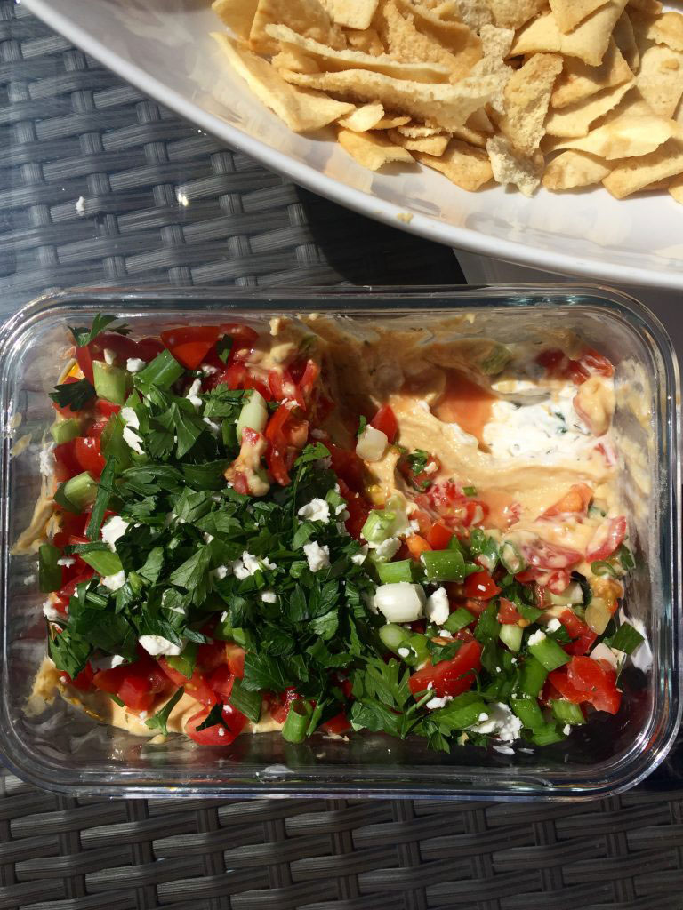 Low Fat 7 Layer Greek Dip served with pita chips and raw vegetables