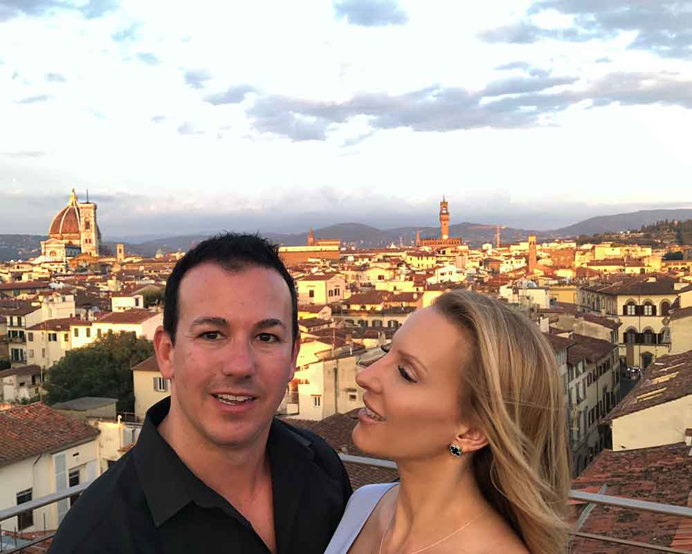 Romantic couple panoramic sunset views Se' Sto on Arno Florence Rooftop Bar.
