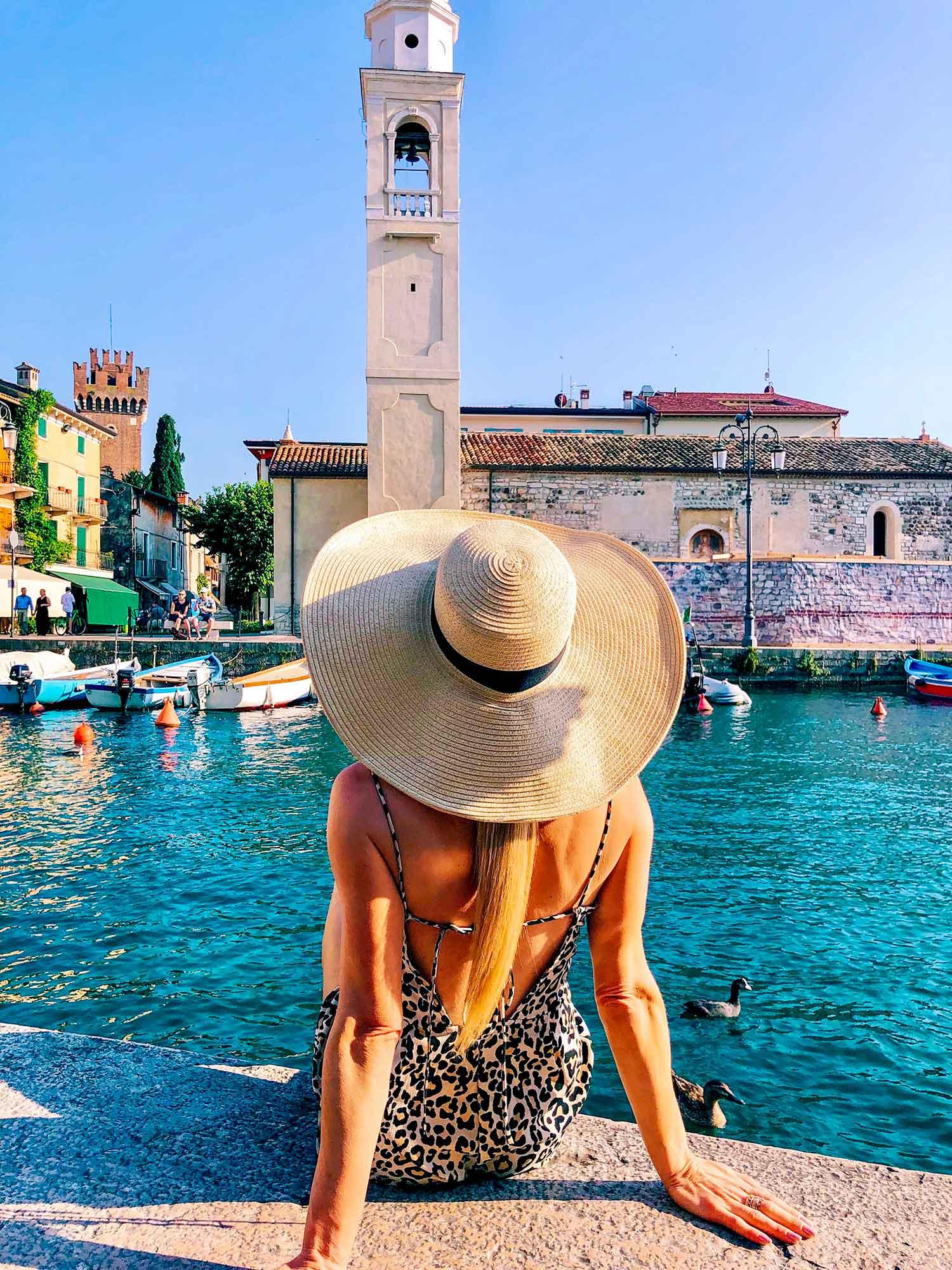 Travel blogger Eve Dawes sunhat sat Lazise Lake Garda Italy sunset