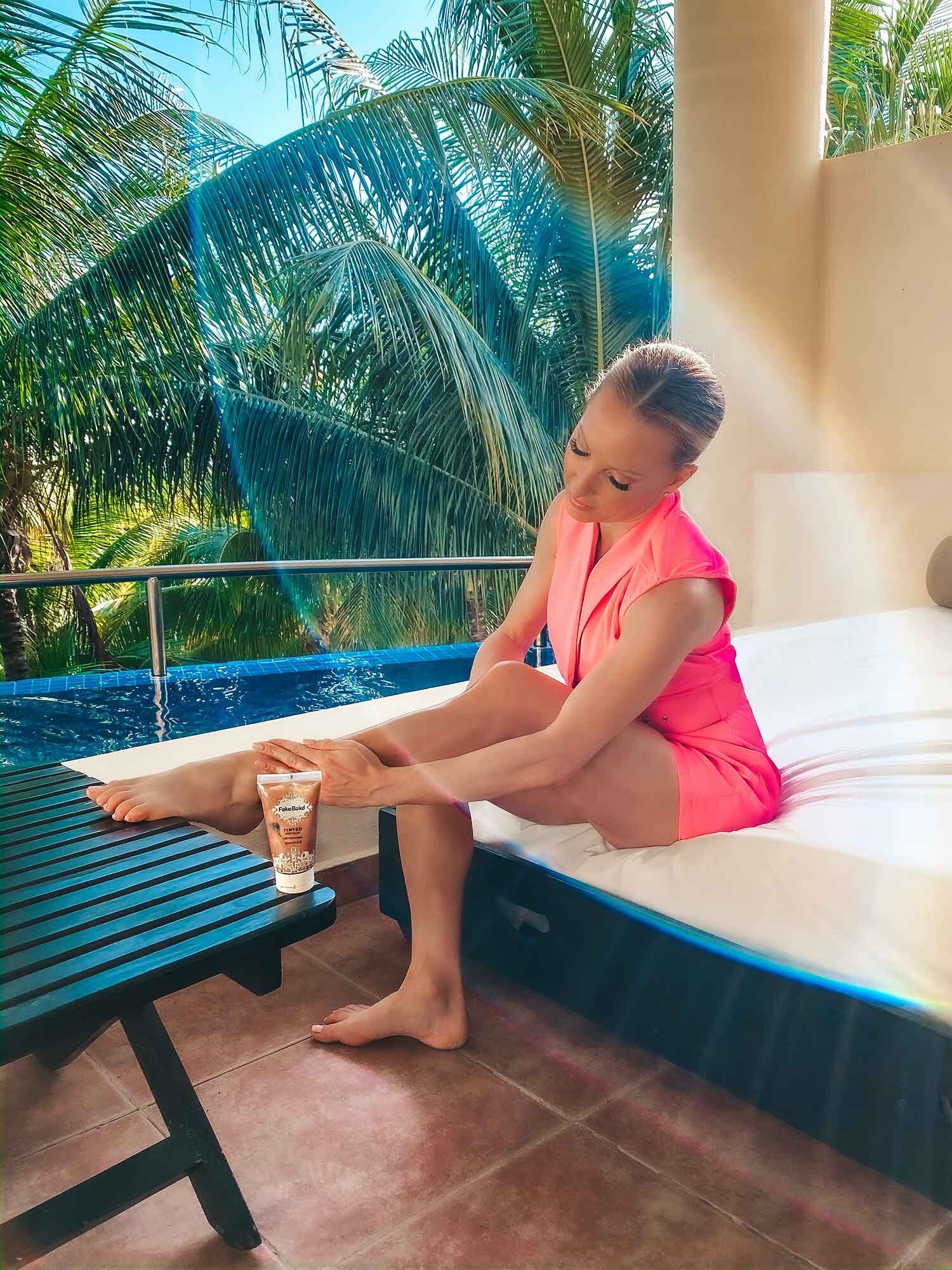 Model applying self tanner balcony El Dorada Maroma Mexico pink romper