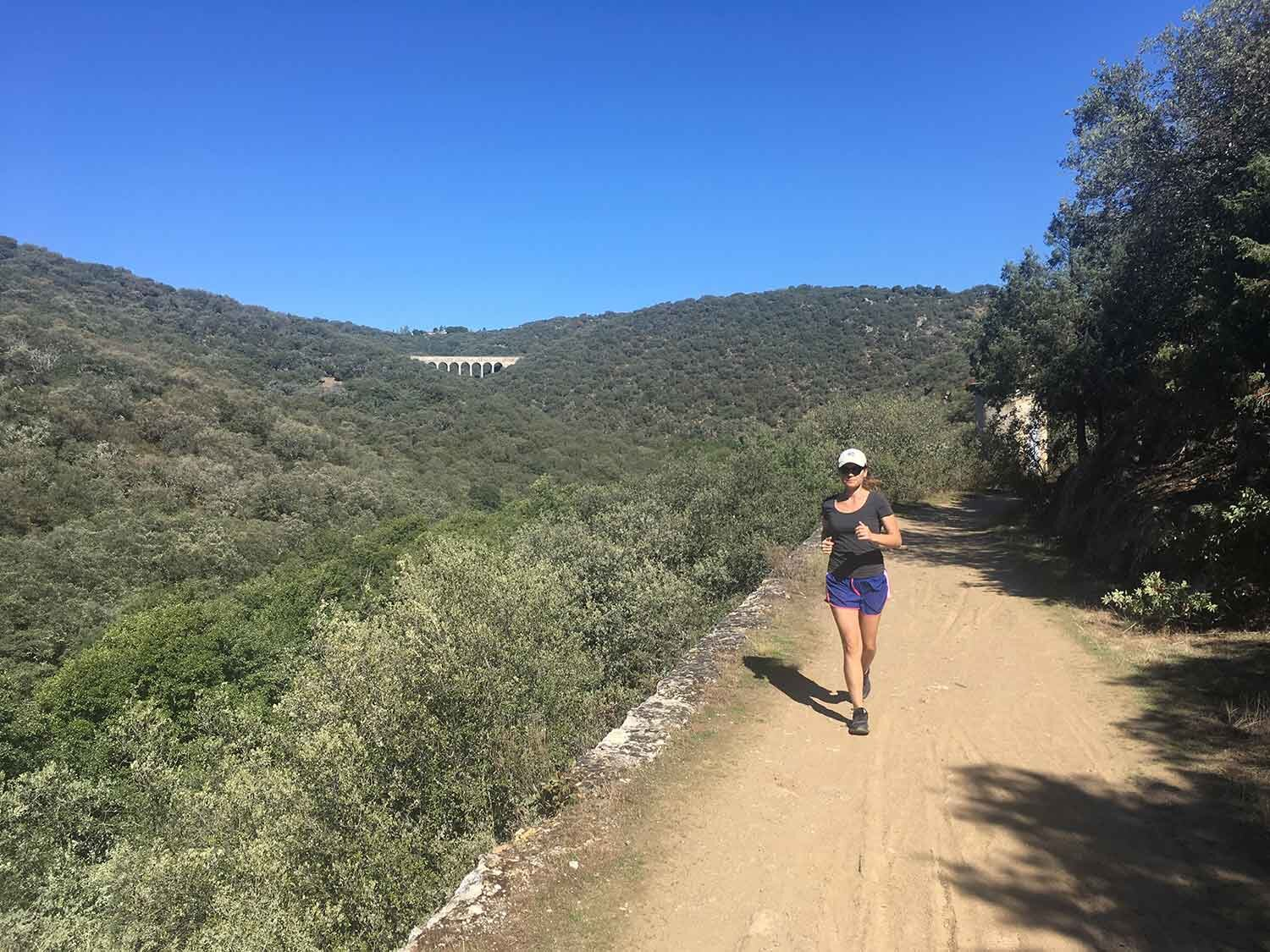Workout Woman running outside sunny canyons