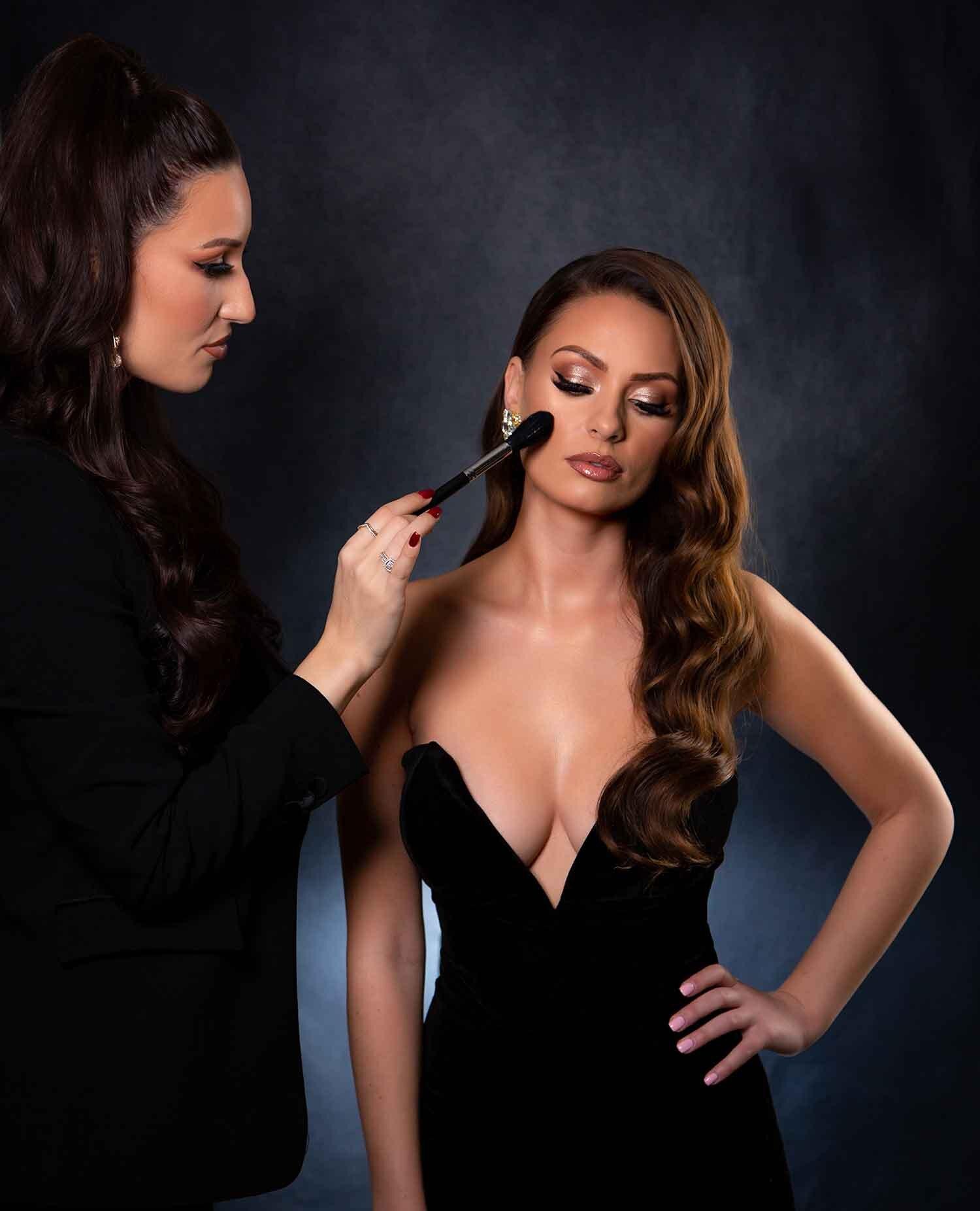 Makeup artist applying blusher brunette beauty model