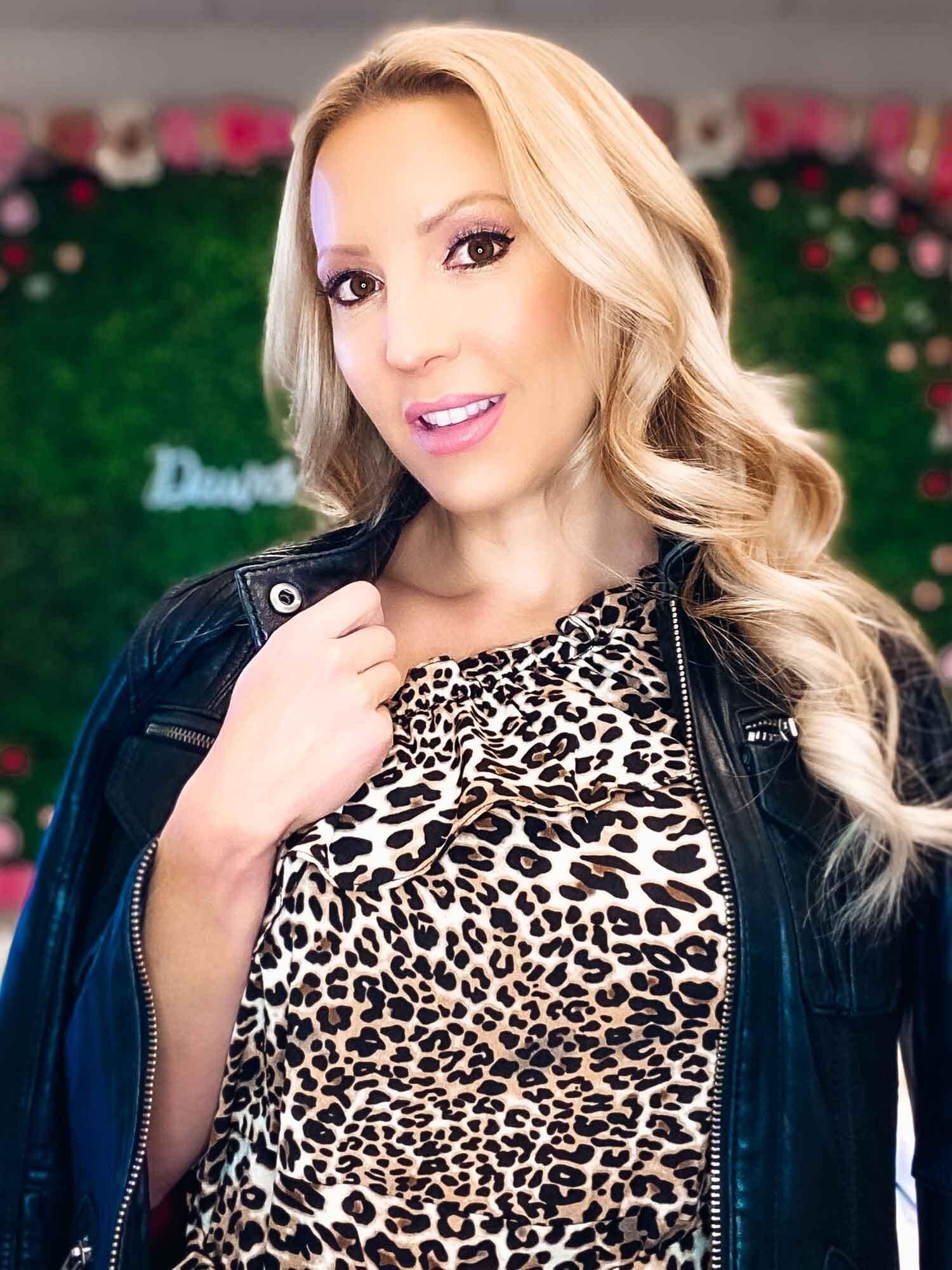 Blonde fitness model Eve Dawes animal print dress black leather jacket