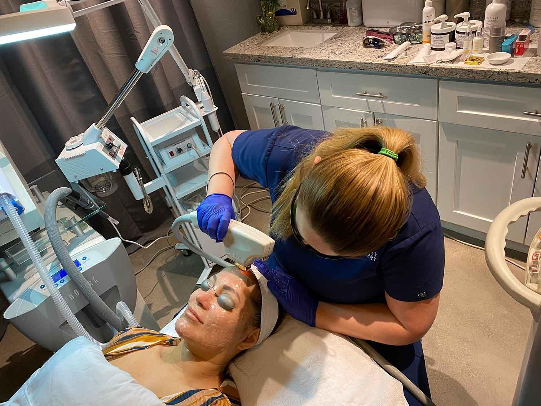 Nurse giving anti-aging laser face treatment botox alternative in office