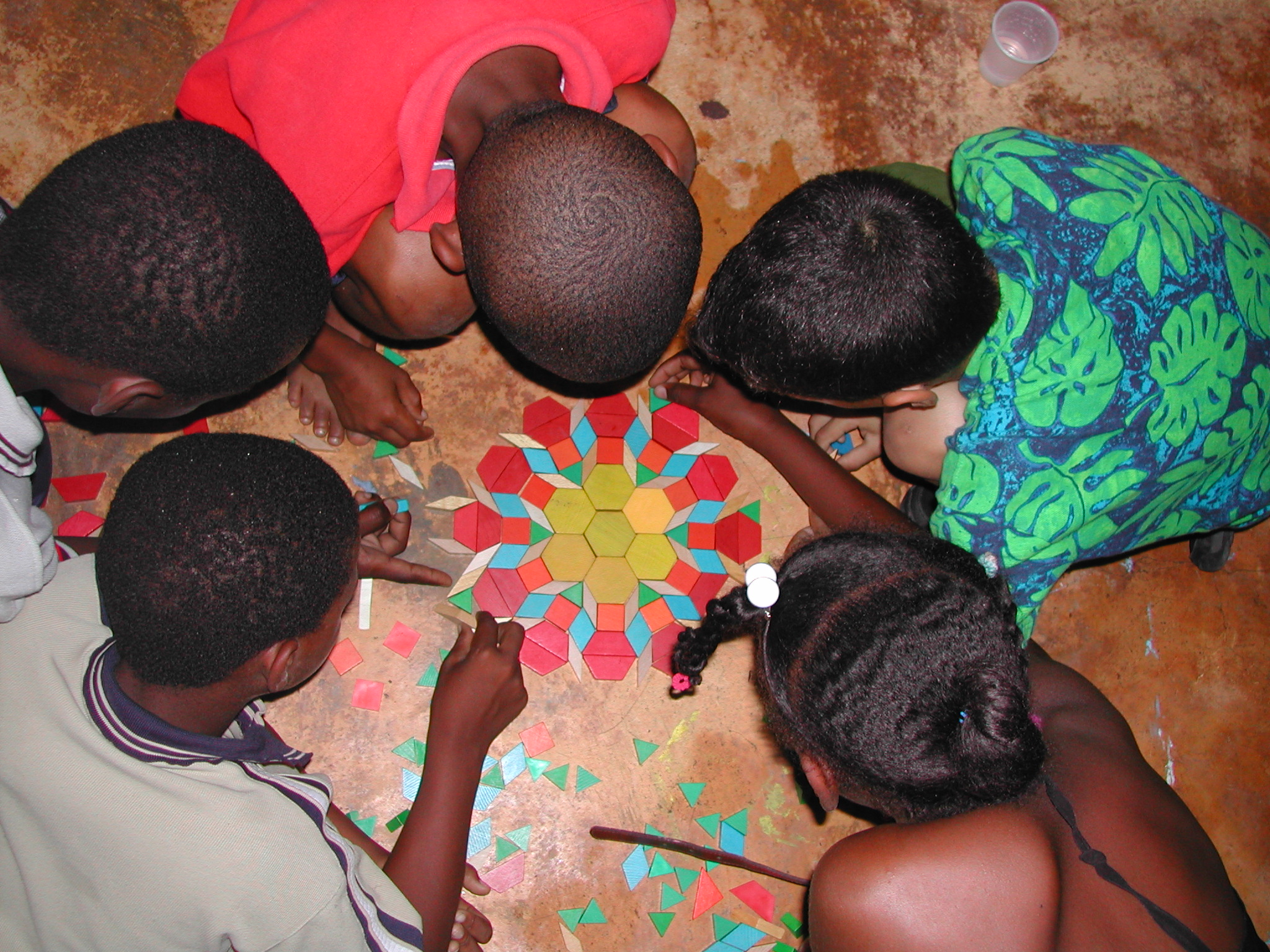 Kids making wood block mandala at summer arts camp, Cruz Verde