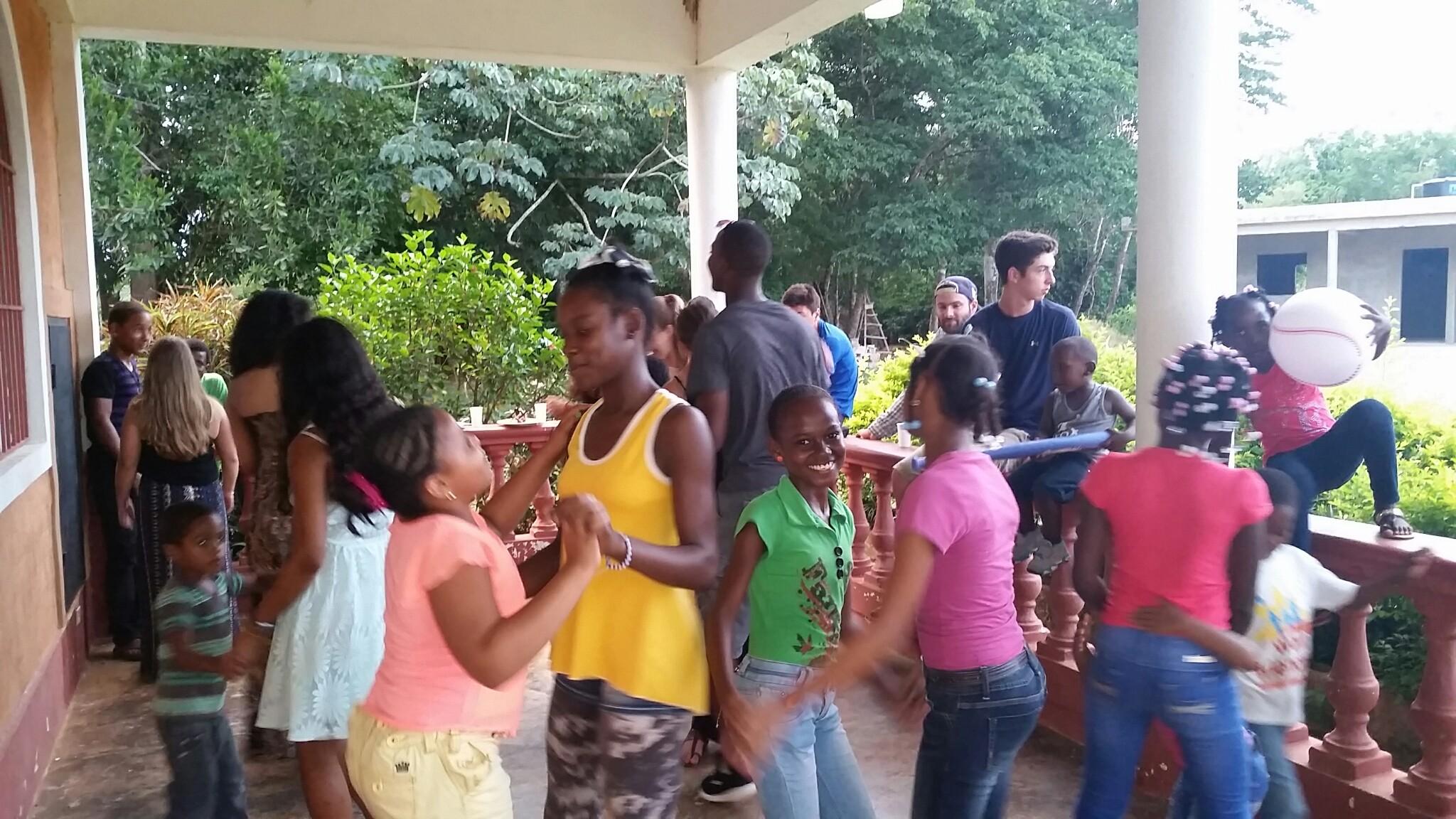 Kids dancing in the gallery of Learning Center, Cruz Verde, afternoon, with volunteers