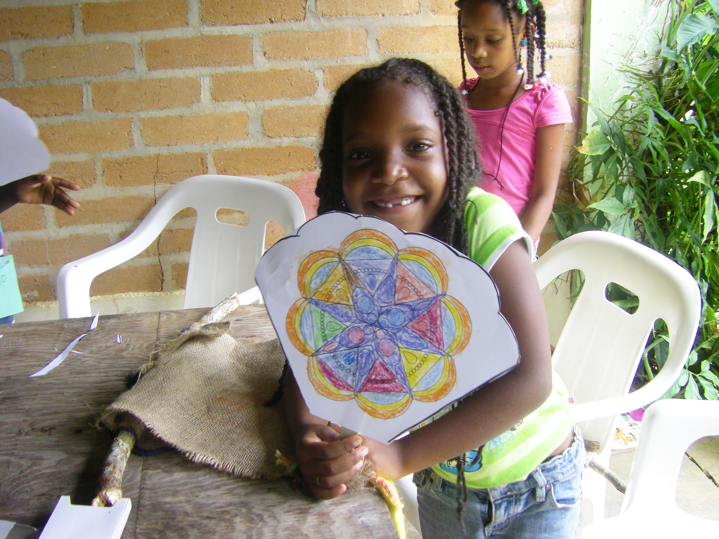 Girl with fan at summer arts camp, Learning Center, Cruz Verde