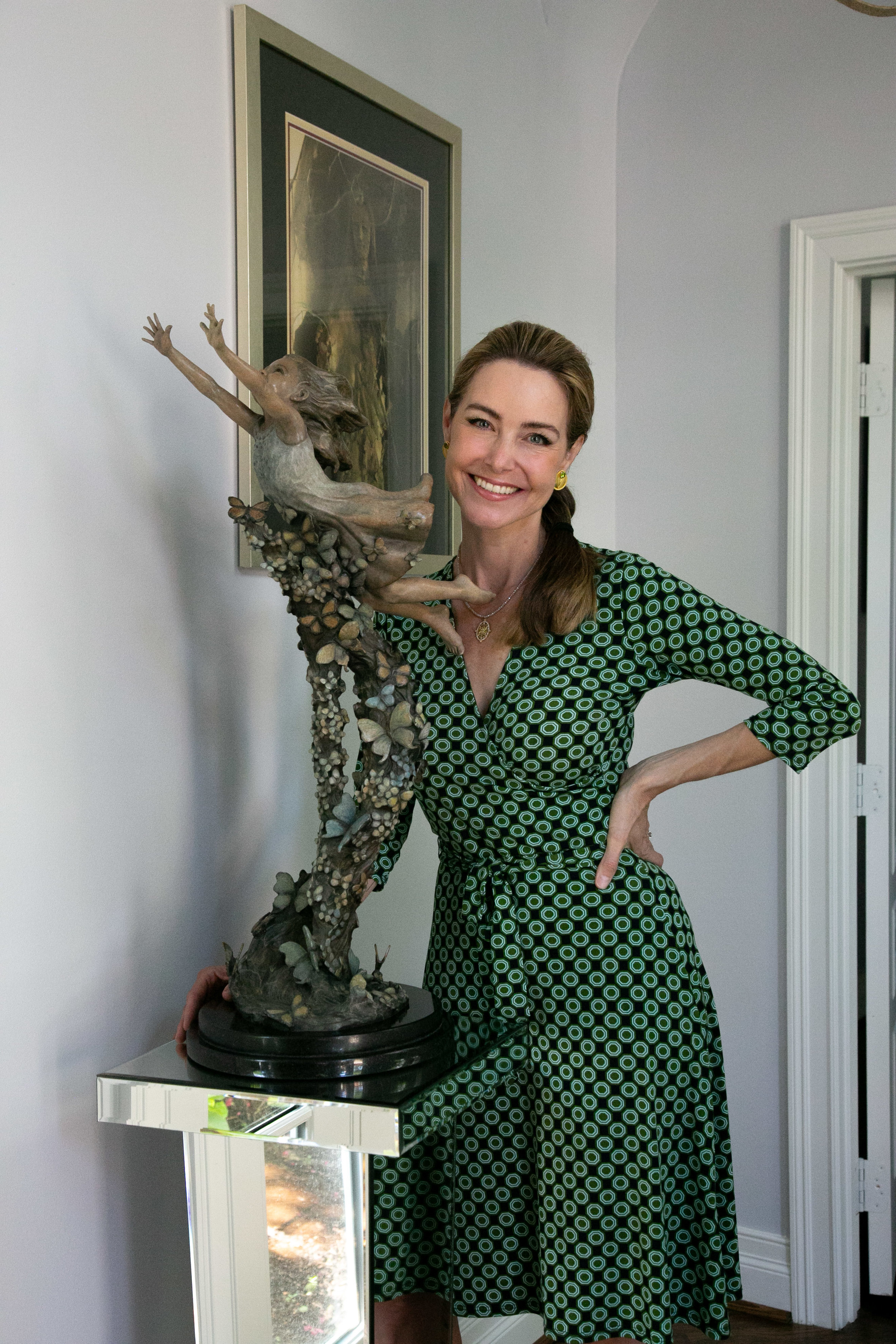 """Angela with the half-life size of """"Lift Her With Butterflies"""" in her home."""