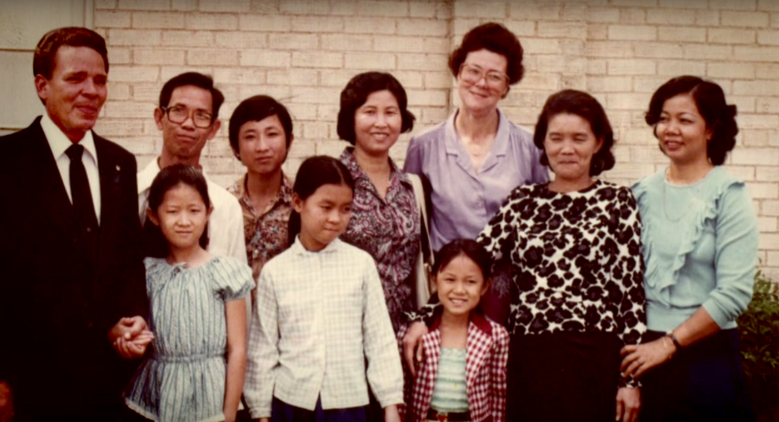 Thear (bottom center) with her family and Catholic Refugee Services staff, shortly after arriving in the United States.