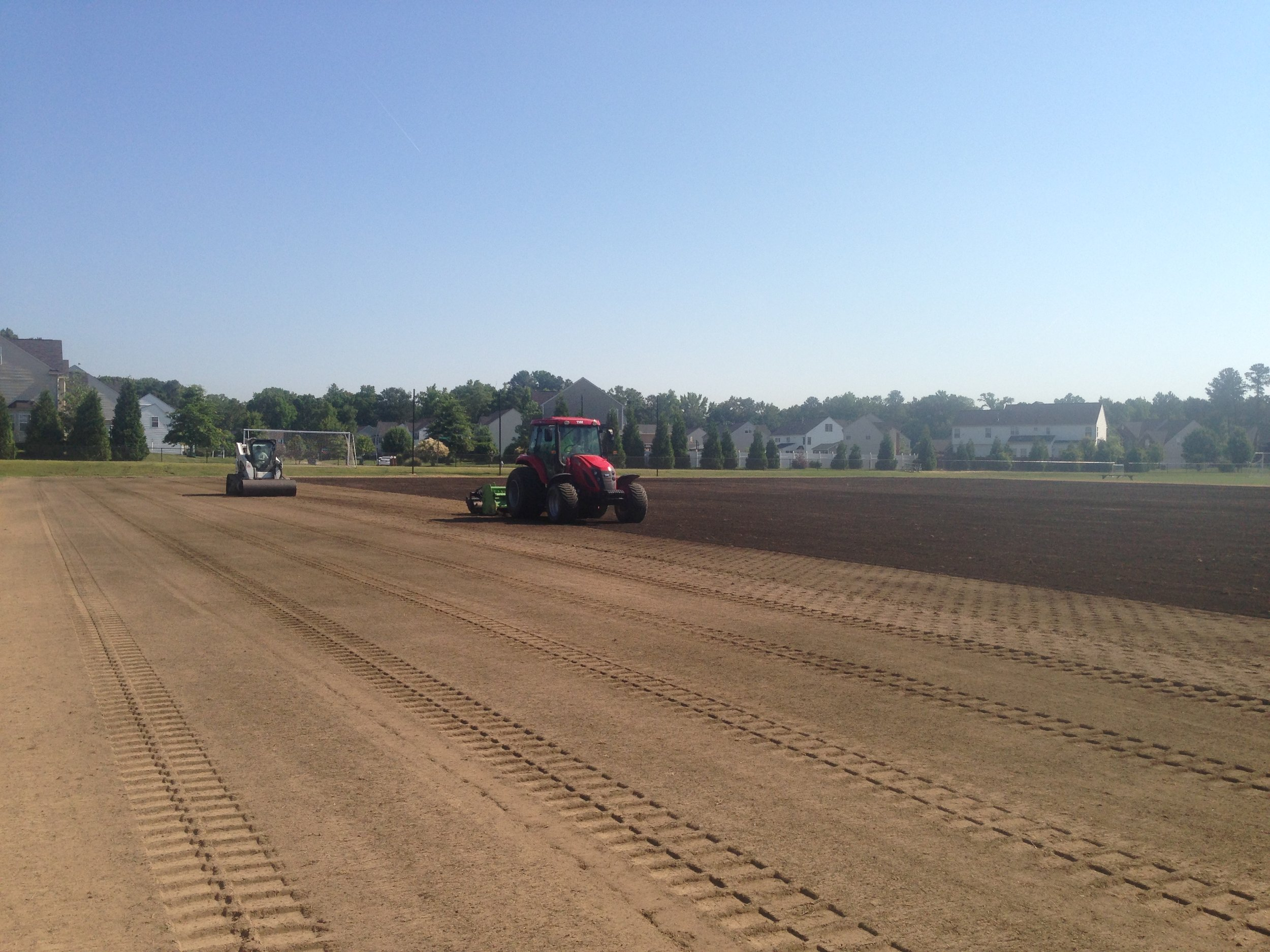 Laser grade phase of new construction sheet drain soccer field.