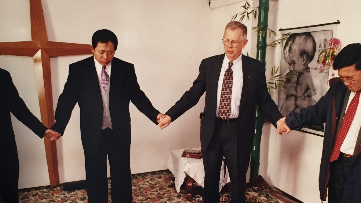 David Bridgman praying with the church in Harbin, China
