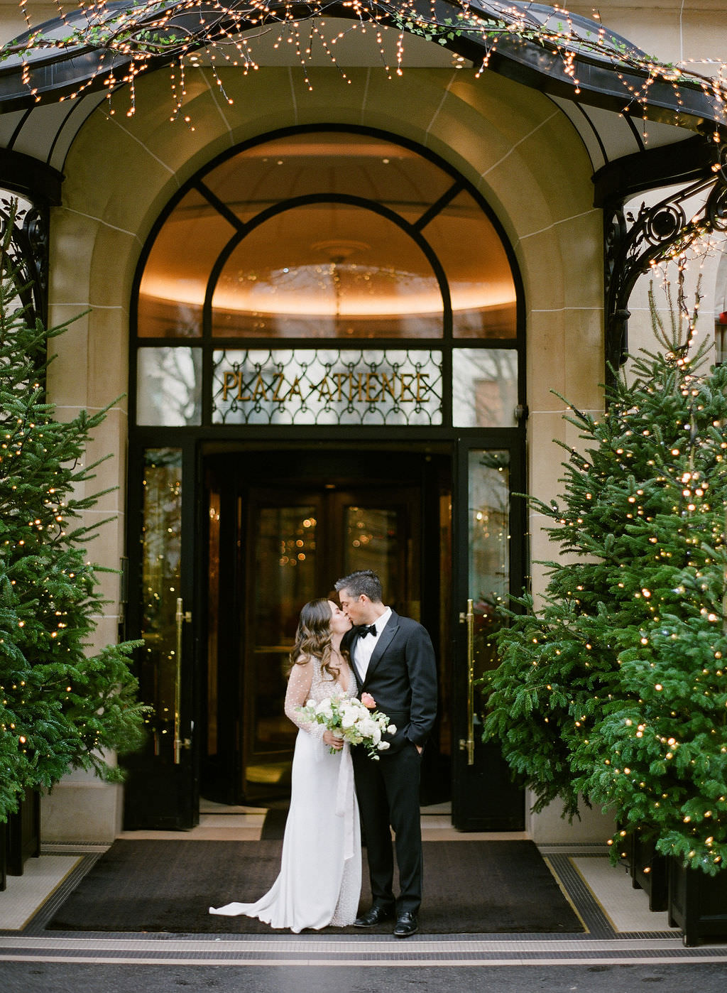 Romantic kiss in front of the Plaza Athenee with lush flowers by  Floraison Paris    Greg Finck Photography