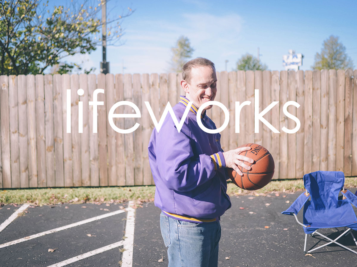 Image of an individual in a purple coat smiling and holding a basketball. They are outside in a gated area. There is a bright blue sky in the background. The word 'lifeworks' is in white, overlaid on the image.