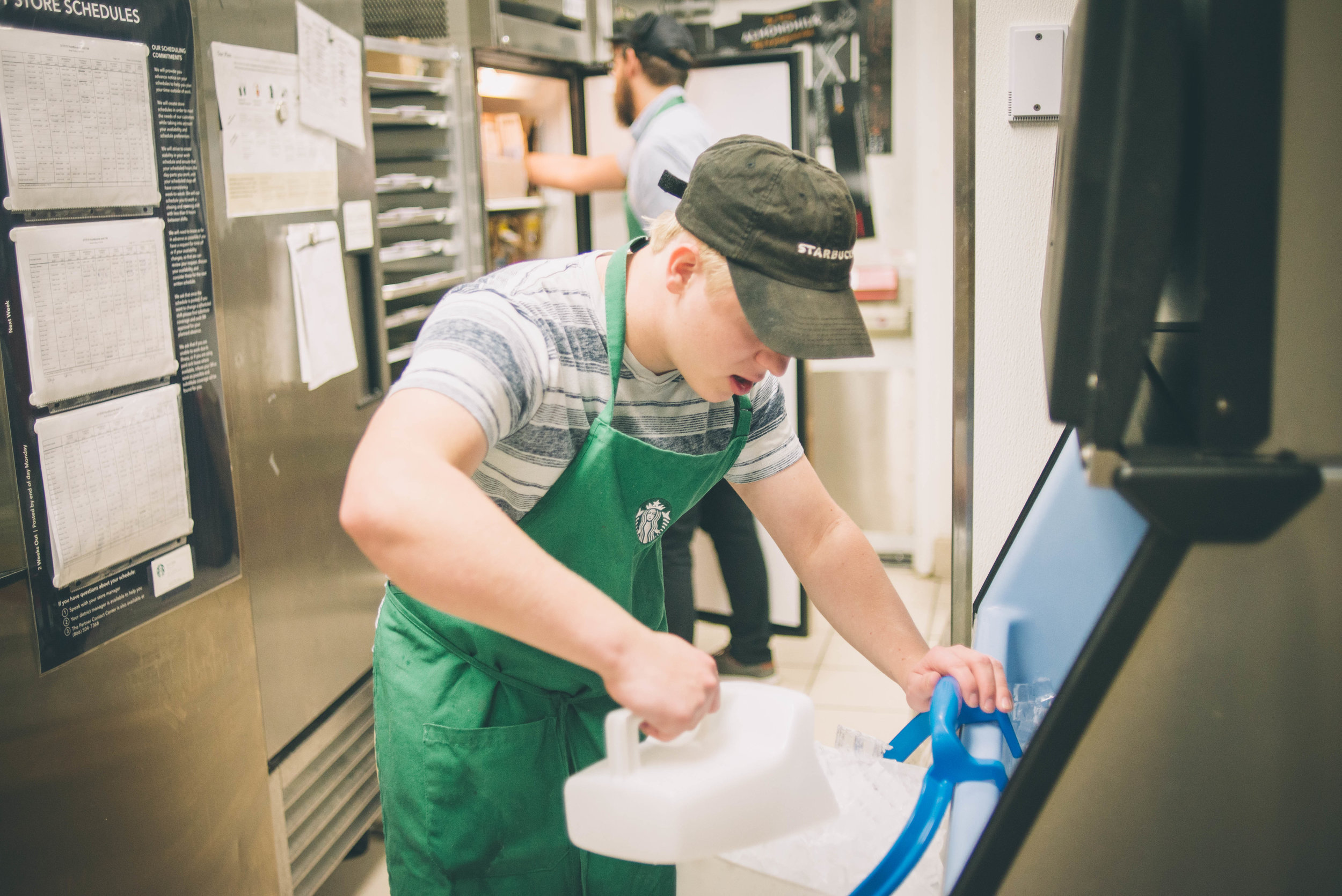 Image of an individual scooping ice out of a ice refrigerator. They are wearing a Starbucks apron and hat with a striped t-shirt. They are in a kitchen area.
