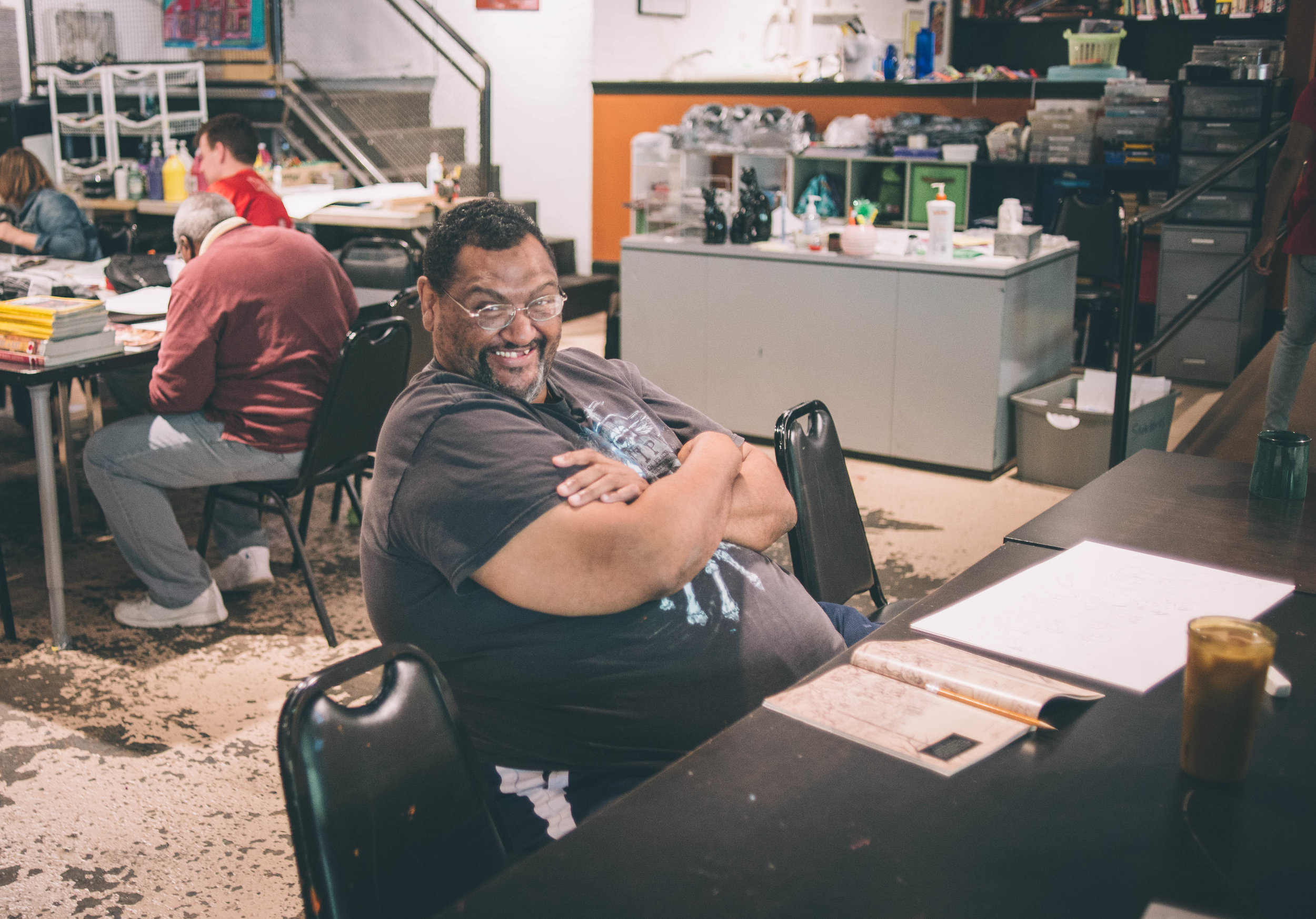 image of an individual smiling and laughing, looking in the direction of the camera. They are in an art studio setting, with paper and pencil on a table in front of them.
