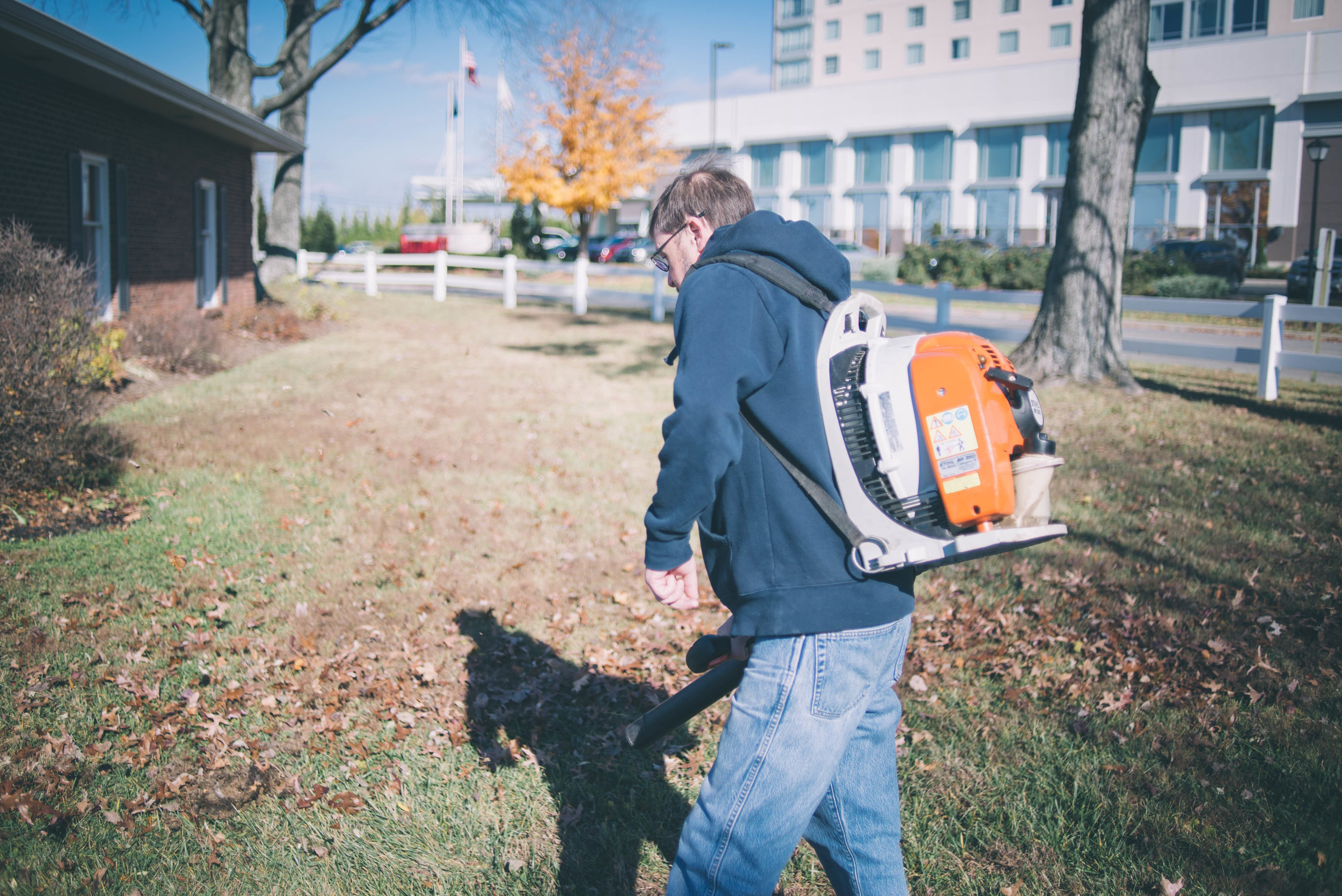 Image of an individual using a leaf blower with their back to the camera. They are outside surround by fall leaves.