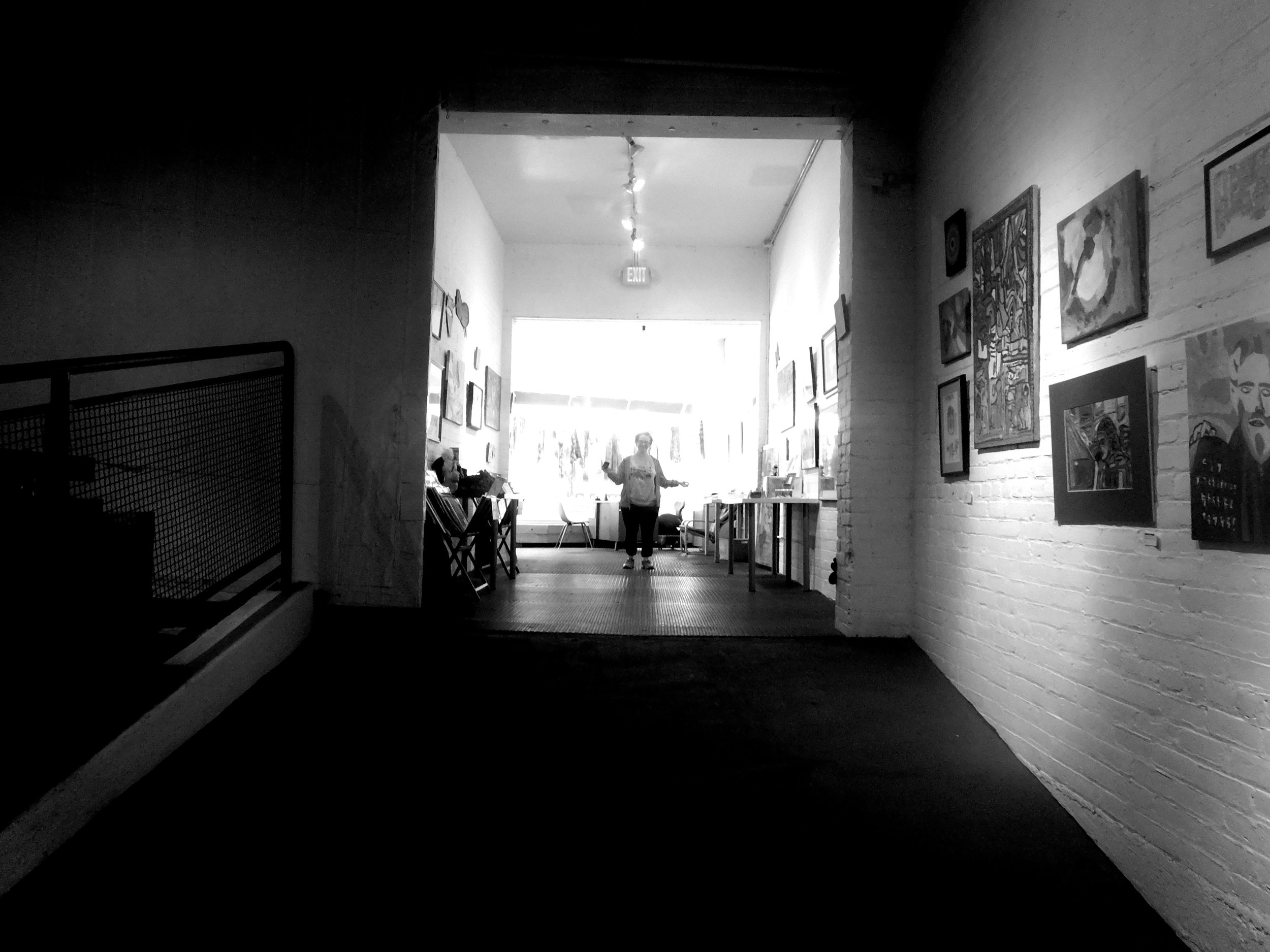 A black and white image of a person standing at the end of a hall. The photograph has stark contrast with very dark foreground, and overexposed background.