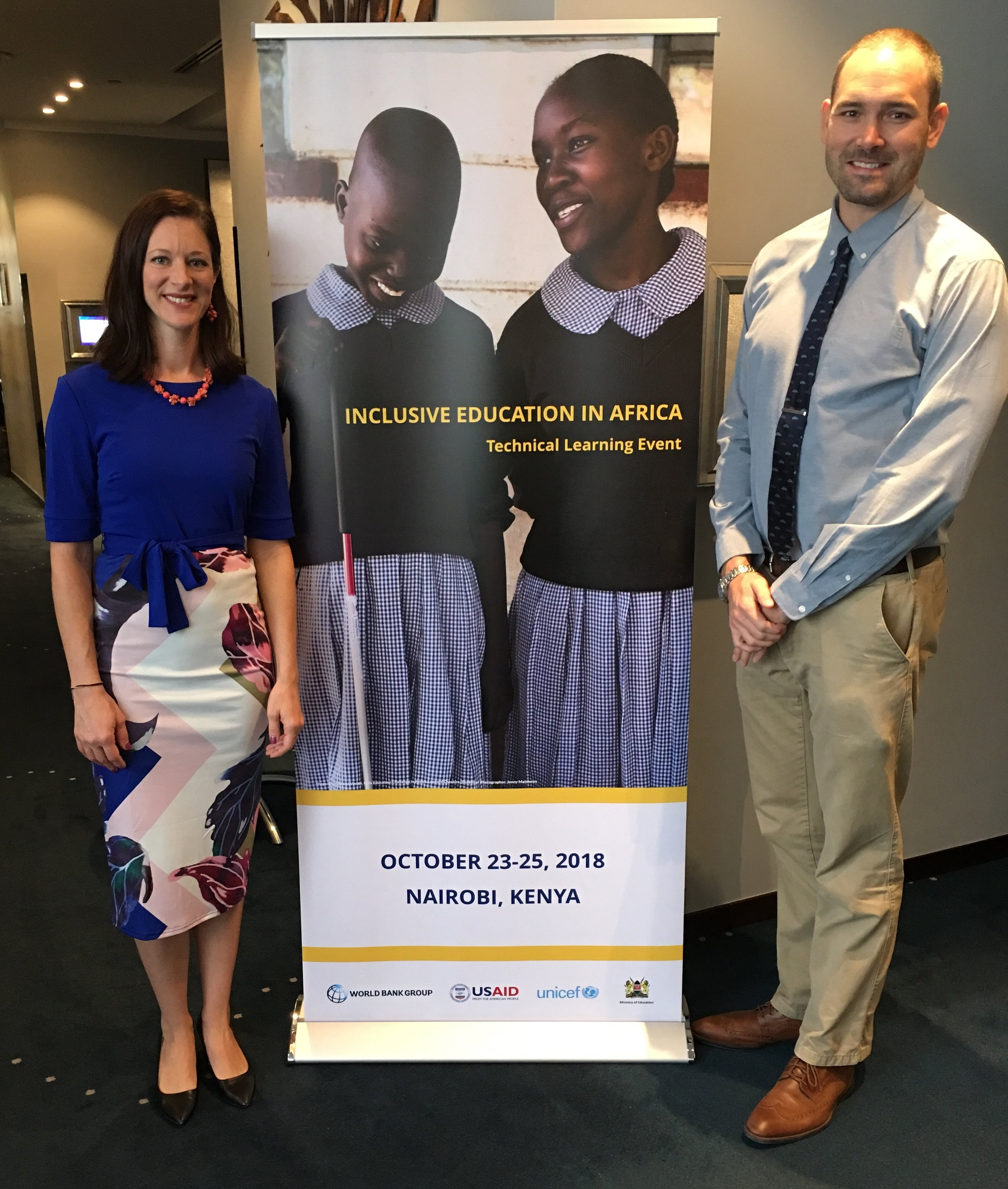 """Leah Maxson of USAID (left) and Brent Elder of Rowan University and Tangata Group (right) standing in front of a poster that reads, """"Inclusive Education in Africa: A Technical Learning Event."""""""
