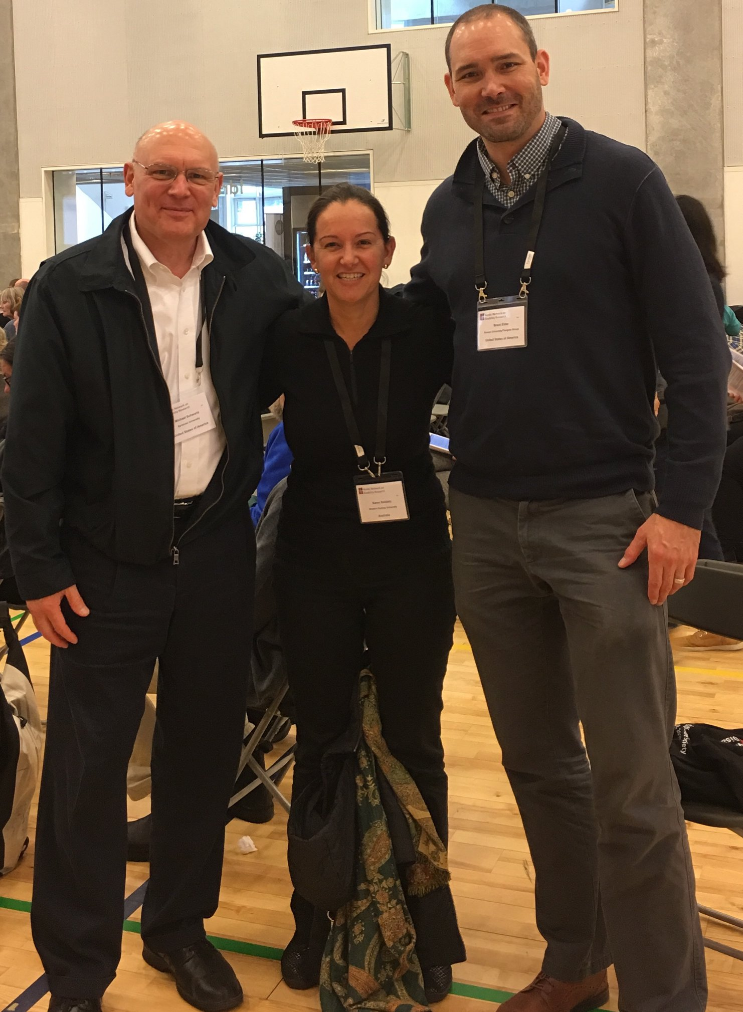 Michael Schwartz (left, black jacket and white shirt) stands with critical disability studies scholar Karen Soldatic of Western Sydney University (middle, black shirt), and Brent Elder (right, blue sweater).