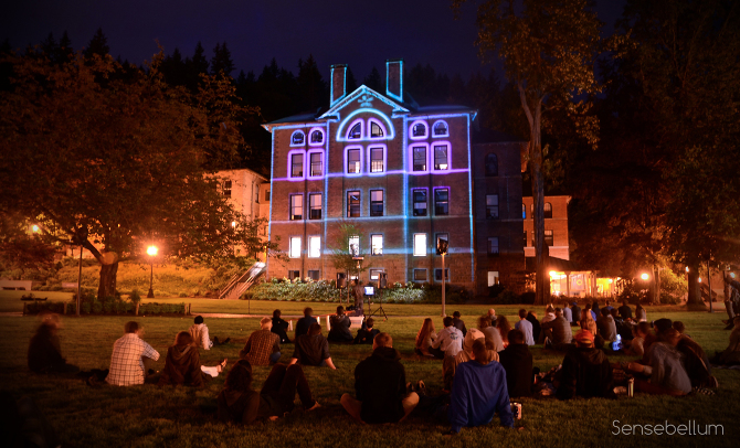 People enjoying the creative projection mapping for the outdoor festival in Bellingham