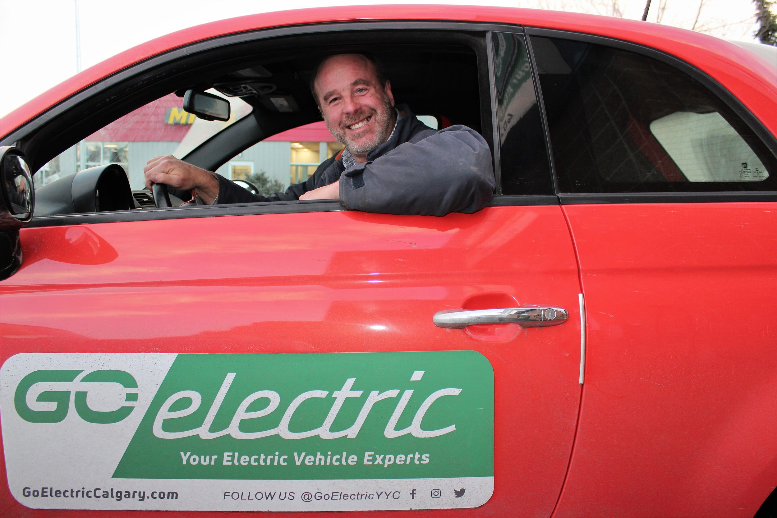 Go Electric co-founder, Jim Steil, with one of his electric car lot models.