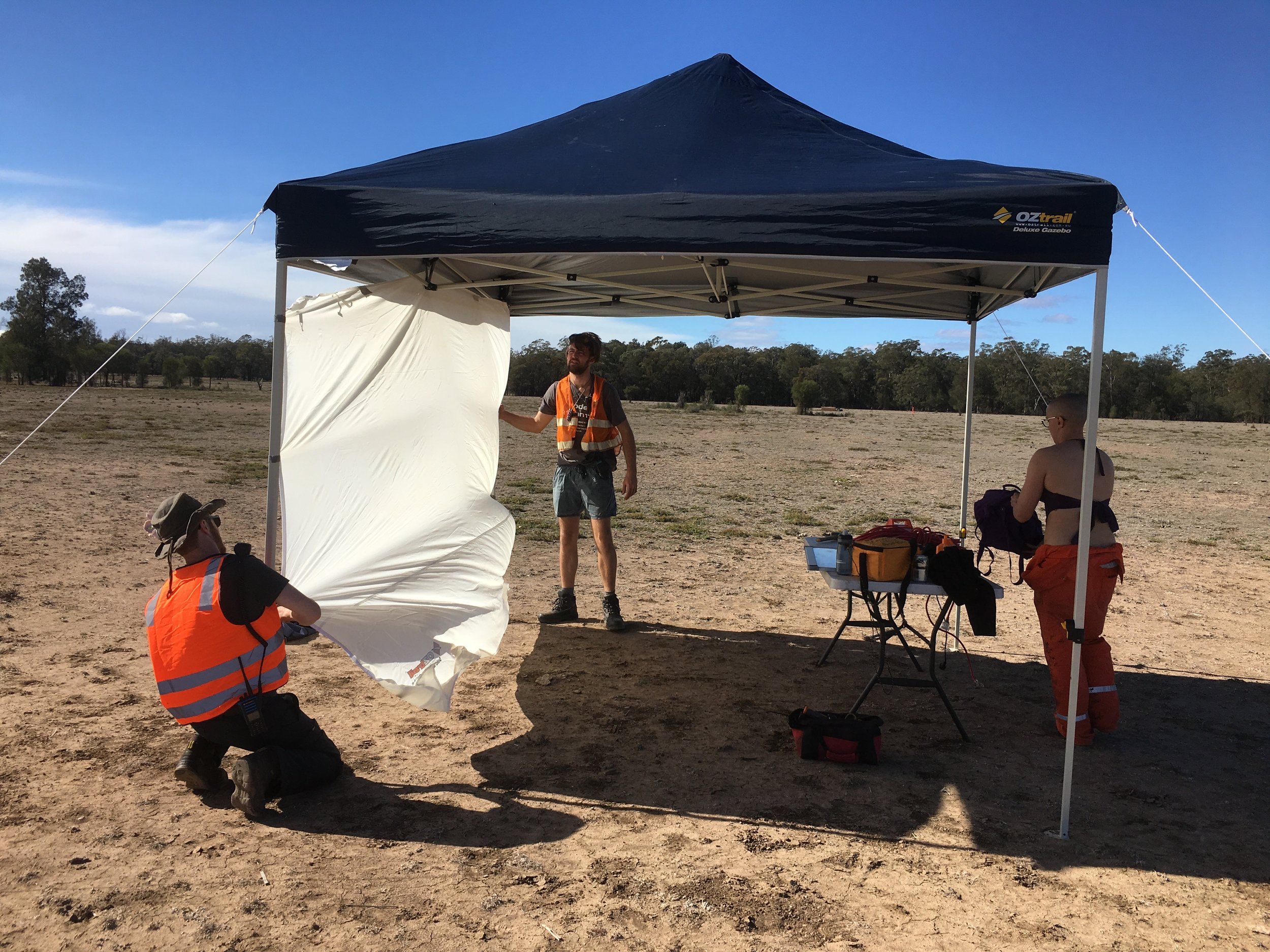 The author (left) giving Tom Brown (middle), effigy lead, a hand getting some additional shade up in the wind, while Jorja Christensen - a blow-in from Perth - gets the tool table set up for the day.