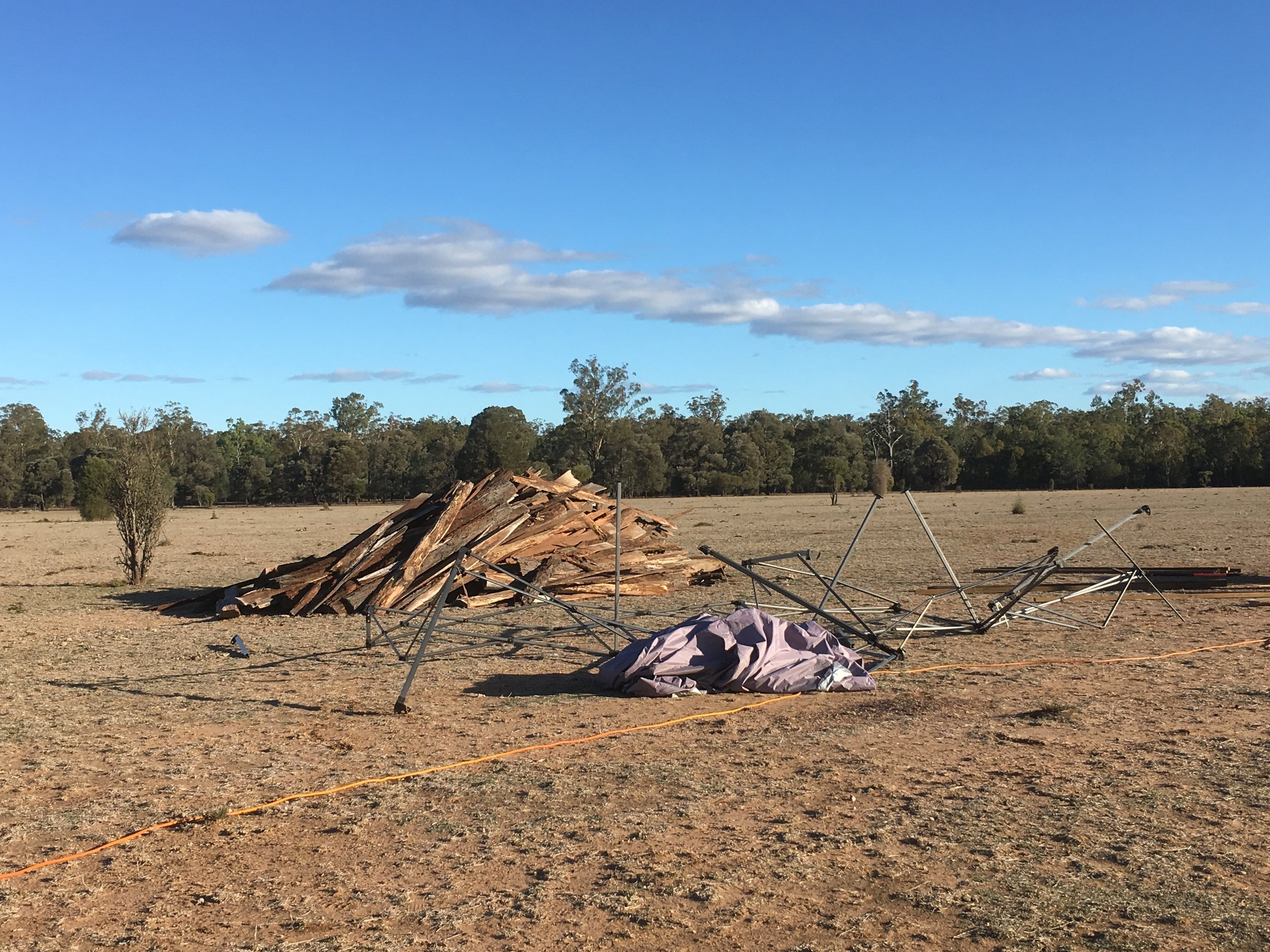 Background: The pile of flitches at the Temple site ready to be sorted. Ironbark is so-called for a reason - each length of bark is a two person lift Foreground: the mangled shade structure that succumbed to high winds the previous day, soon to be carted off to the local tip.