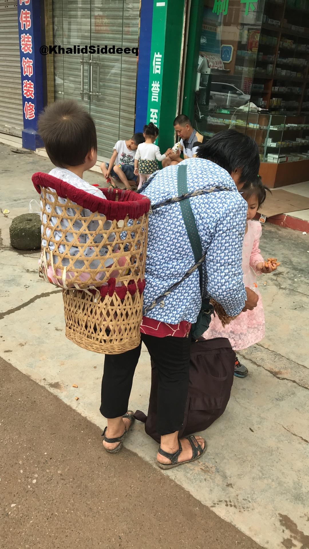 إمرأة تحمل طفلها بطريقة تقليدية