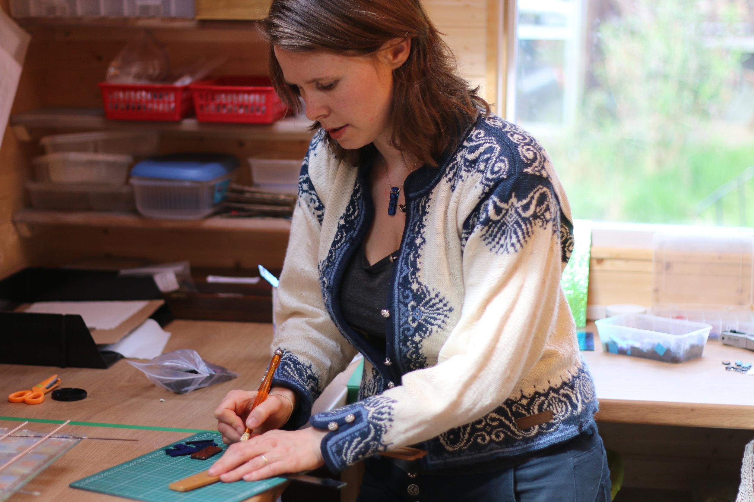 Mere Glass Designer Maker Hannah cutting glass in Studio