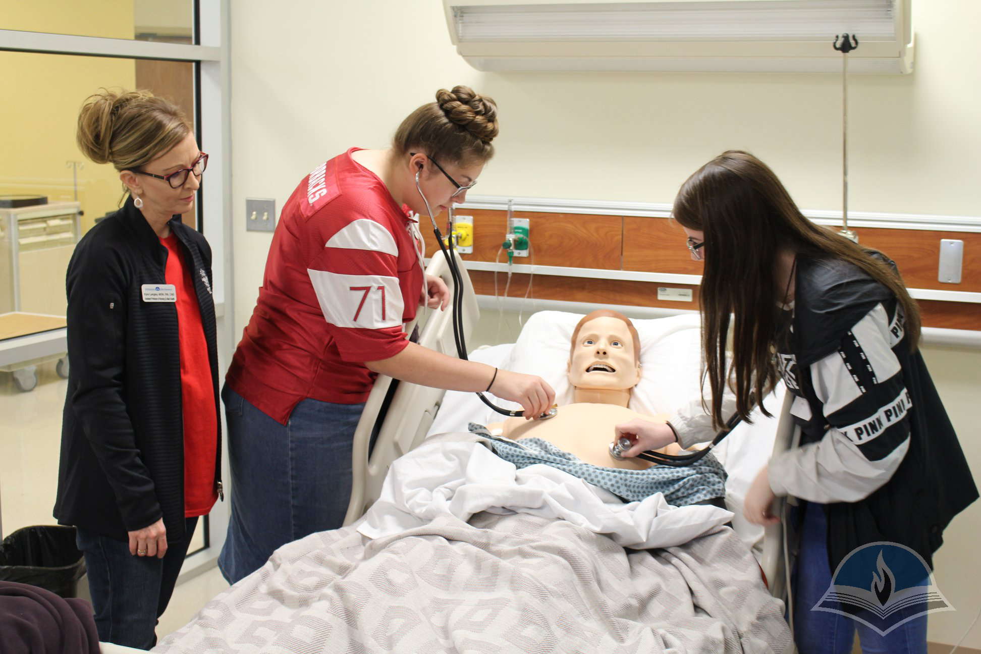 Arkansas Northeastern College STEM Camp for Girls participants learning to take vitals in a nursing simulation lab.