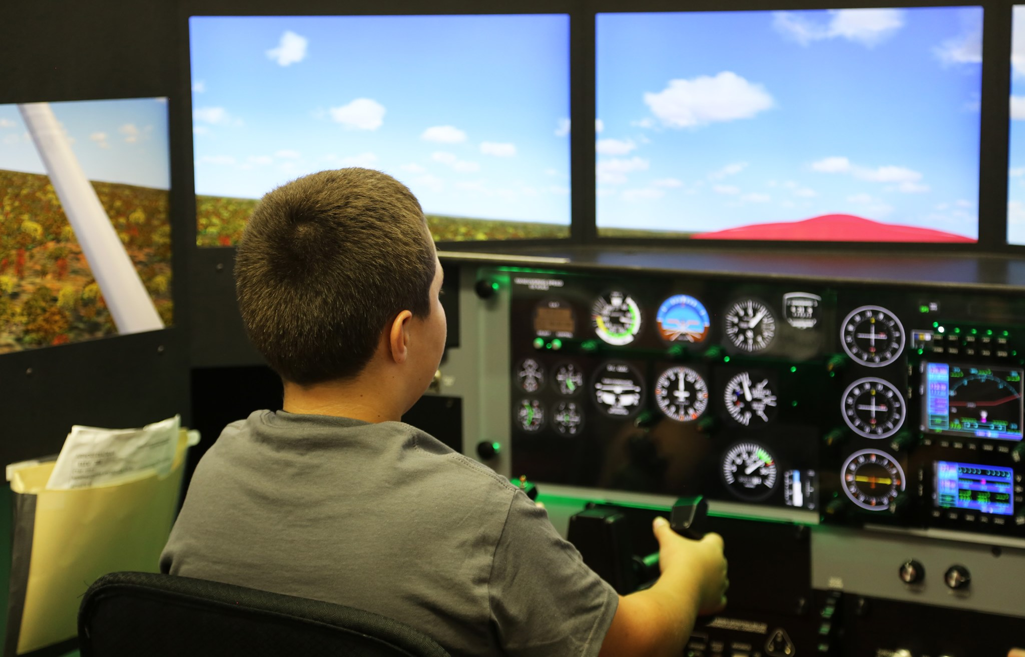 An Ozarka Aviation Camp participant practicing his flight skills in the simulator.