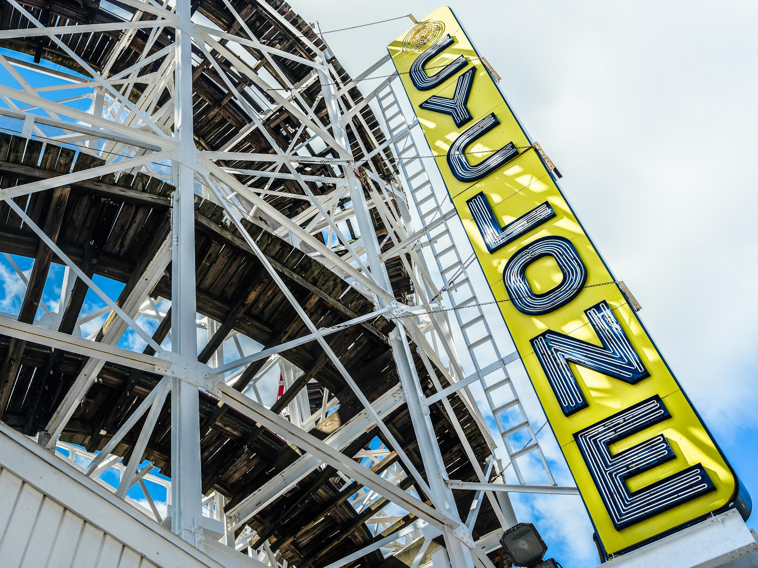 Yellow Cyclone sign with view of tracks - they were running tests with empty roller coaster seats while I was there