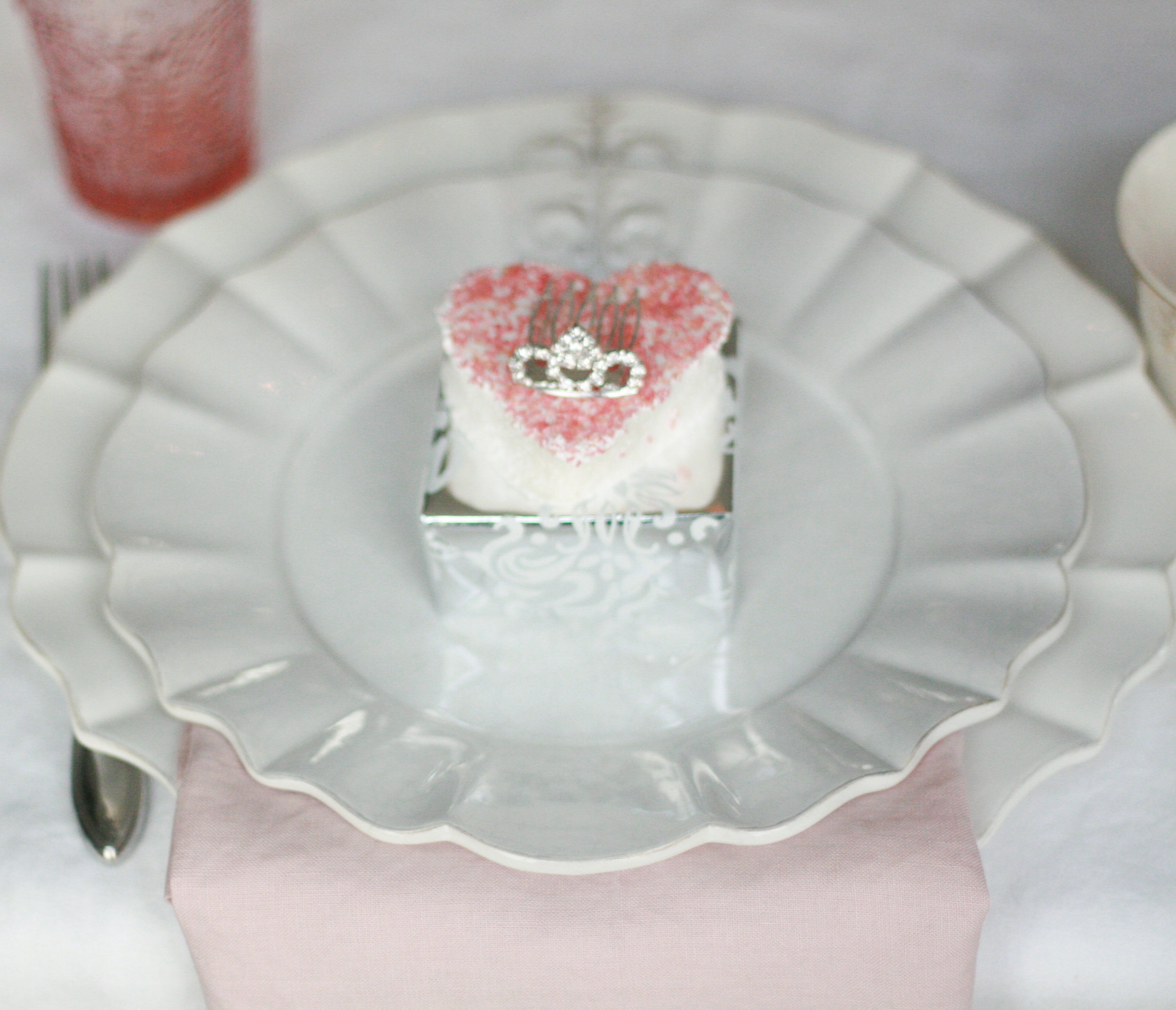 The party favors were little dollhouse miniature  cakes  and  tea sets , and little  tiaras  atop the marshmallows.