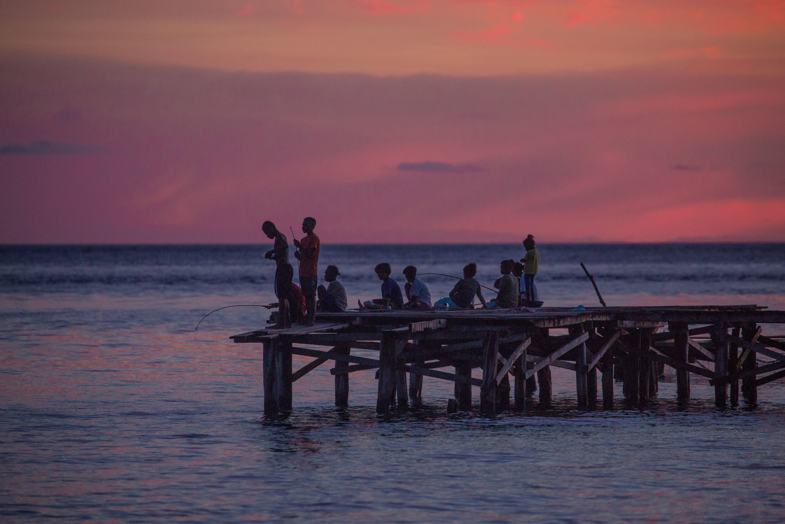 jetty in Sawinggrai, gam island - As we were saying goodbye to the elders of the village and to our guide, the horizon had turned a bright pink and orange, reminding us of how much we were going to miss this remote paradise at the tip of the Bird's Head Peninsula in the West Papua province. Meanwhile the kids and teenagers in the village were out playing soccer, going in for a dip, fishing and having fun. People have lived in Raja Ampat for a long time in balance with the nature around them. Their vision and traditions protected the biodiversity of the area while at the same time providing for their needs. Although much has changed in the last two centuries, some sense of balance is returning to the region, and economic alternatives like responsible tourism can help communities benefit financially from the protection of nature.