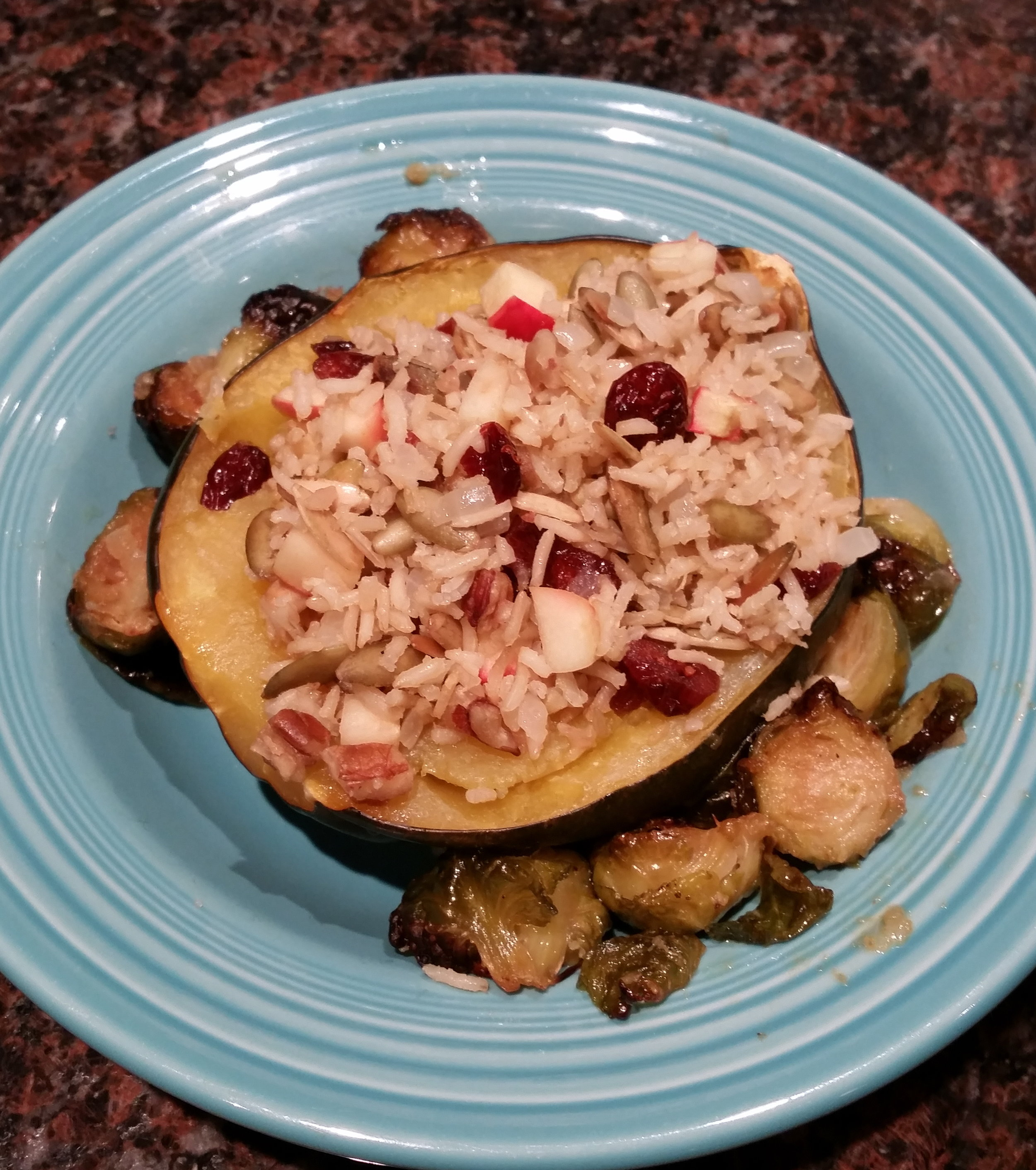 Acorn squash baked with maple syrup and stuffed with brown rice, pumpkin seeds, pecans, apples, cranberries and served with a side of garlic-broiled brussels sprouts. I mean… dang. V/GF