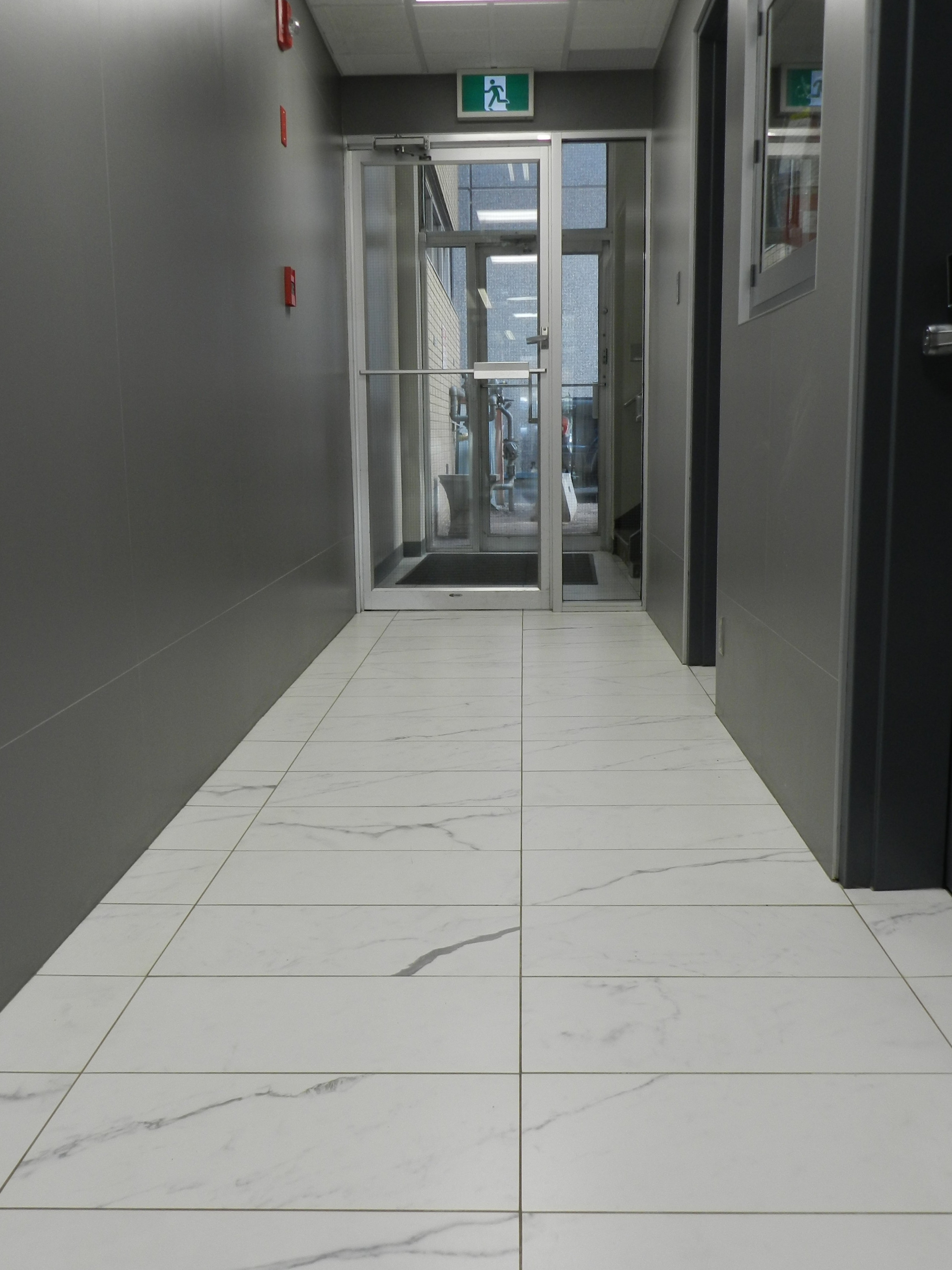 A large format marble-look porcelain is fresh and modern. The walls of this entry are covered in a graffiti resistant tile. The outside of the building has this too.