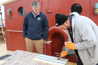 Dan O'Connor from Jamestown Distributors instructs a student in the application of varnish. (Photo credit: Lisa Goodwin)