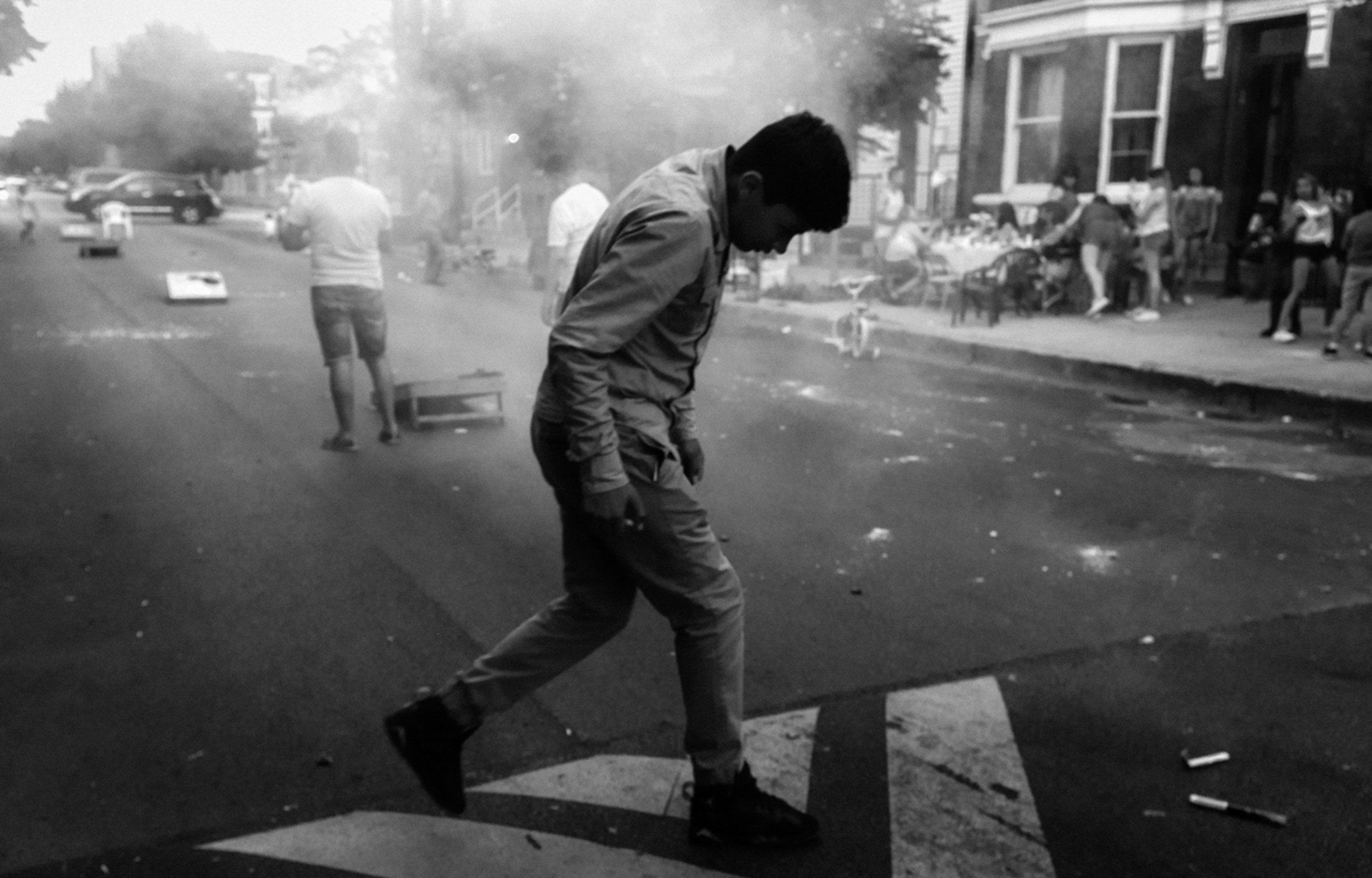 A boy walks through smoke on the fourth of July in 2017.