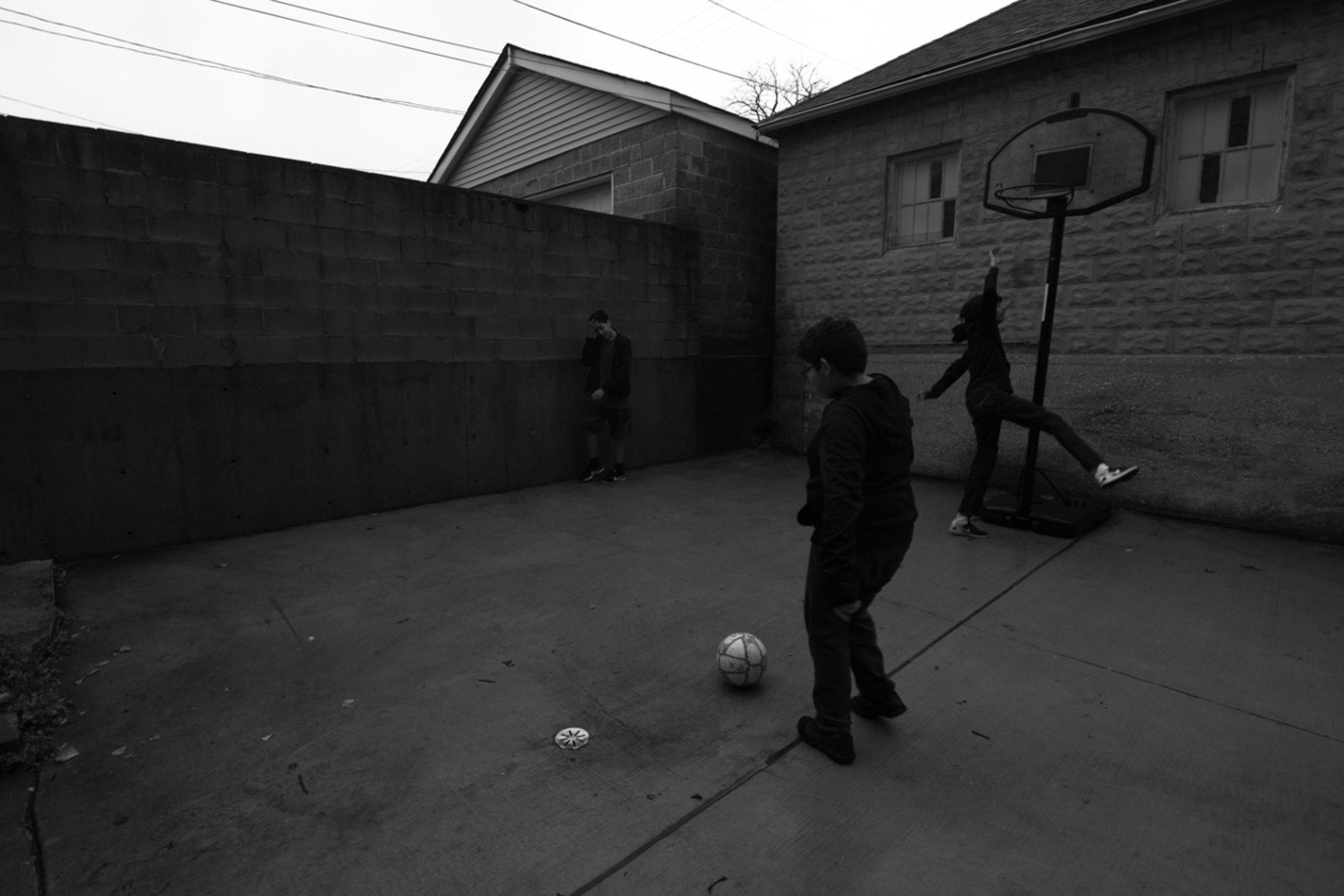 Children play soccer in the rain in their back yard on Nov. 04, 2017 in Pilsen.