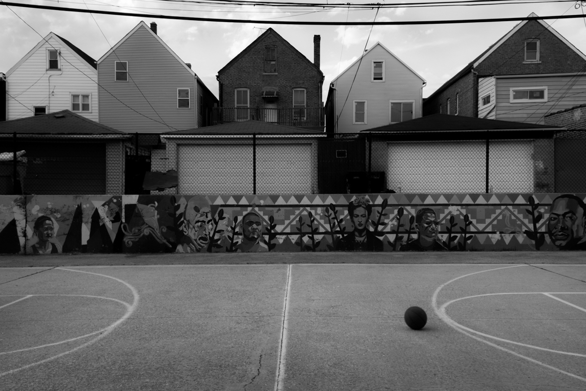 A basketball court surrounded by Barrett Park's murals of public figures.