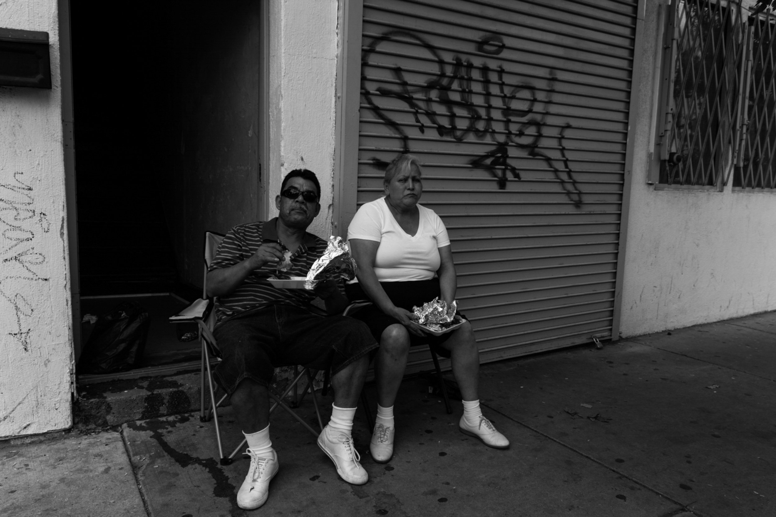 Two community members sit and eat on Blue Island, the neighborhood's pervious commercial strip.