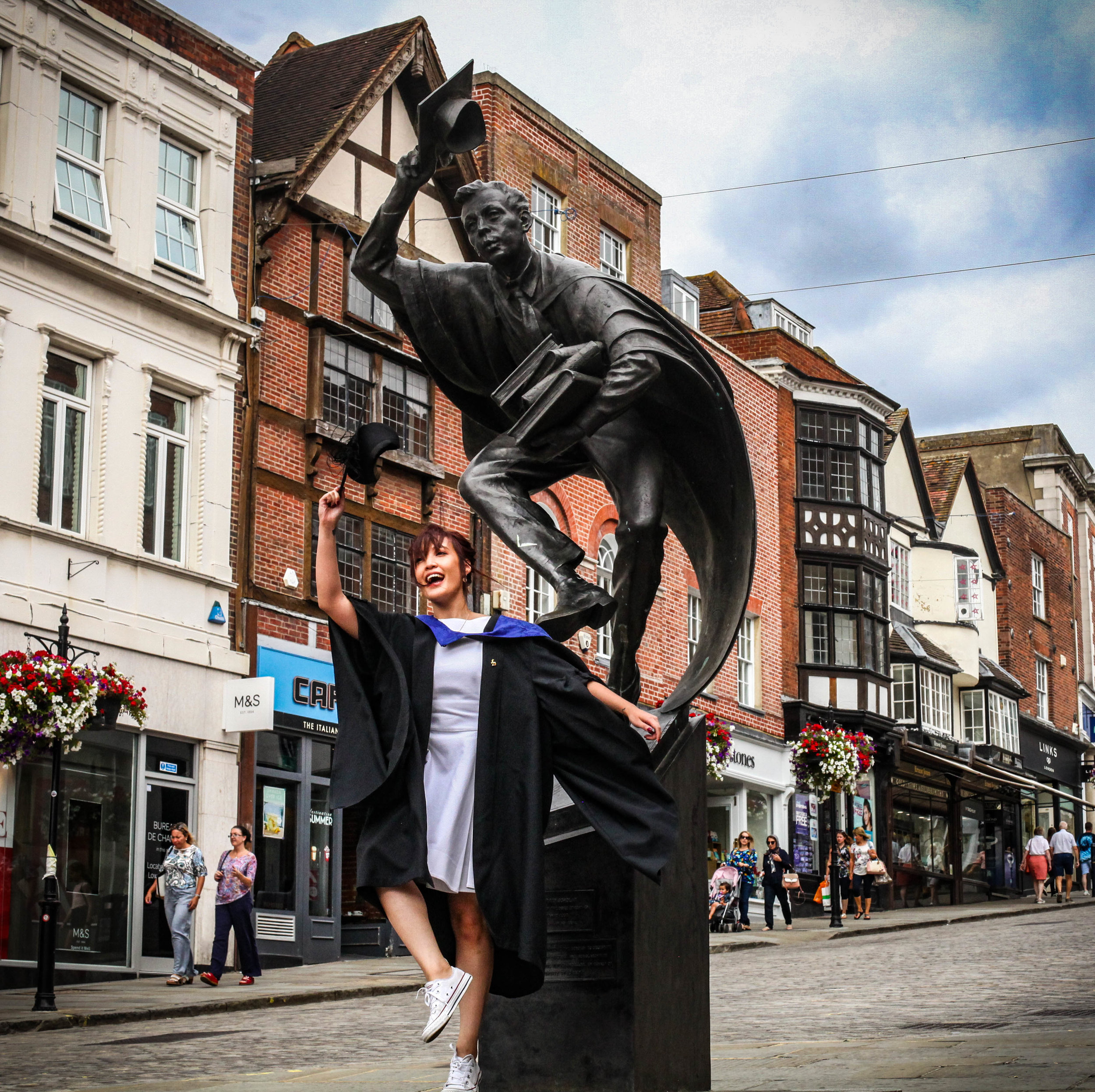 Just an Asian girl in a graduation gown casually trying to mimic a statue in the middle of town centre, that's all XD