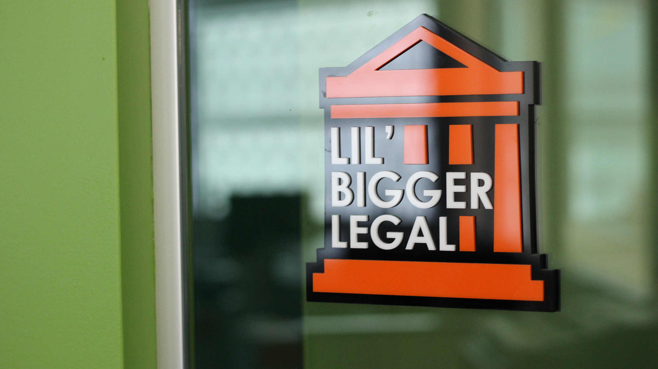 "Conference Room Sign   The Legal Team within QL needed a conference room sign for their private room. They chose the name ""Lil' Bigger Legal"" since this was the new expanded version of their previous room ""Lil' Legal."" Their building had bright orange and green colors, so I used orange in the sign to contrast with the surrounding green wall."