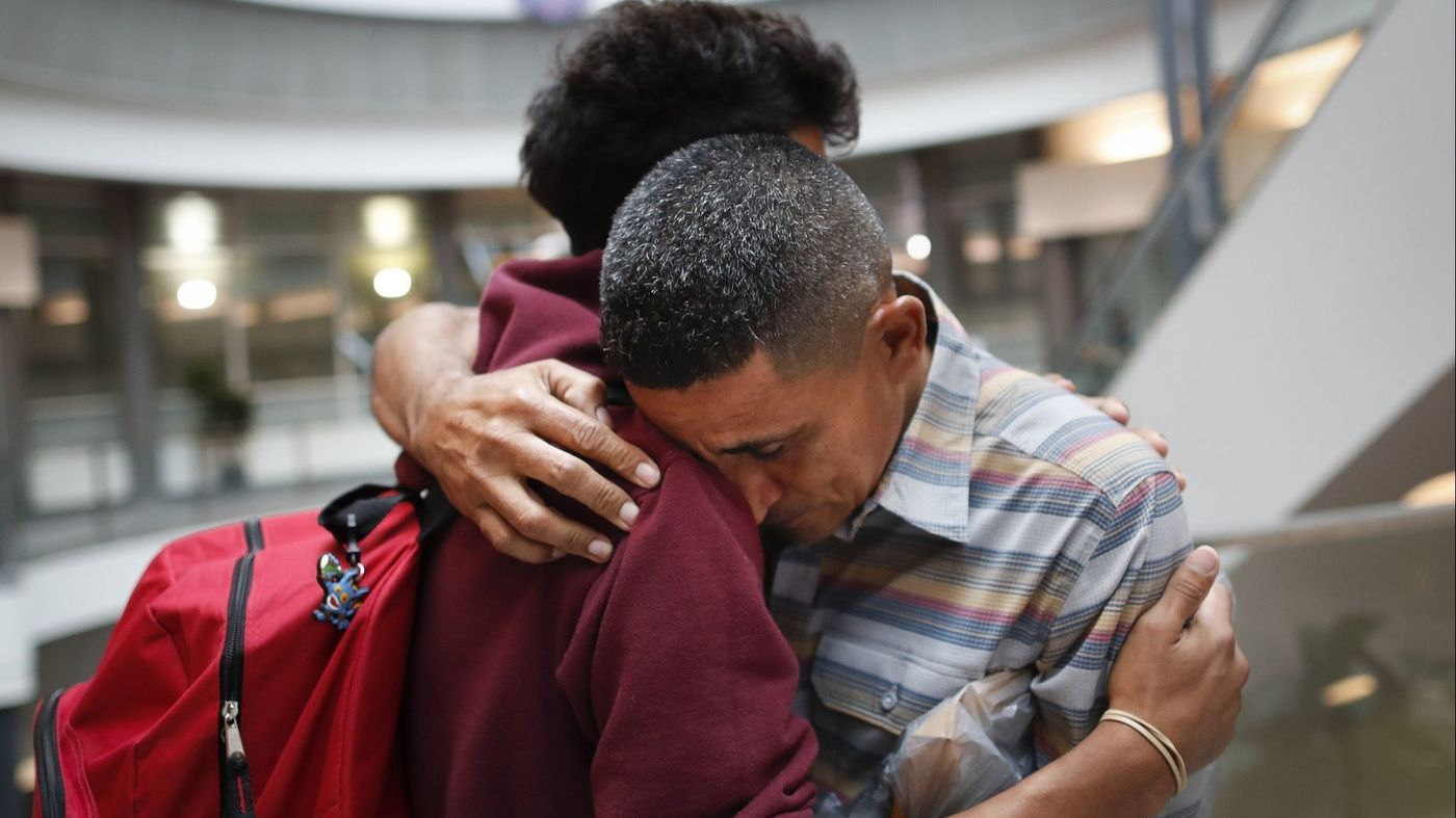 Edvin Cazun, right, and son Samuel of Guatemala reunite in Cincinnati on July 23, about a month after they were separated when they crossed the Rio Grande into the United States. (John Minchillo / Associated Press)