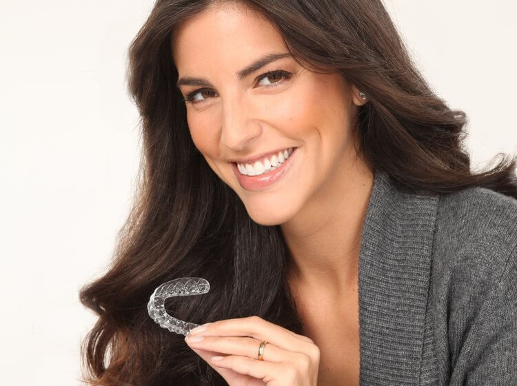 Young female smiling with straight teeth holding invisible aligner like Invisalign