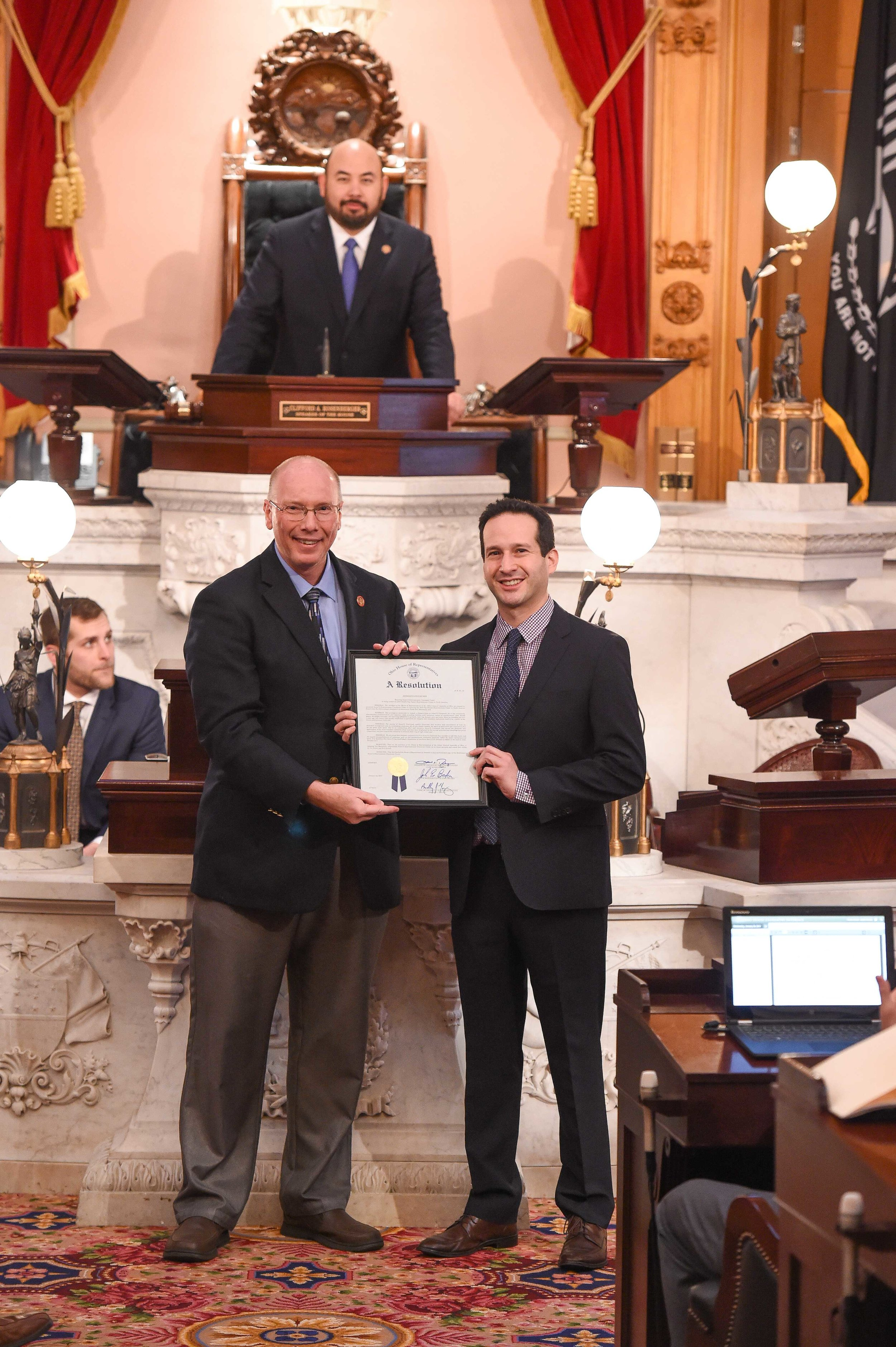 Ohio State Representative John Becker (R-Union Township) presents the resolution to Scene75 Entertainment CEO Jonah Sandler with Speaker of the Ohio House of Representatives Cliff Rosenberger presiding in the chambers.