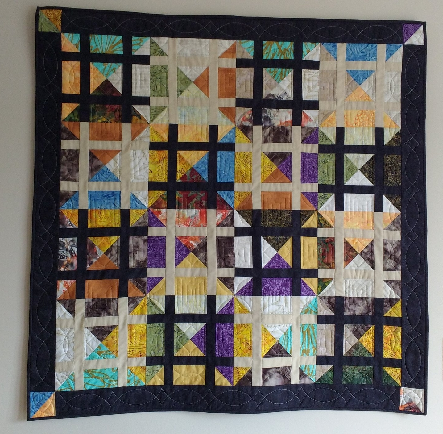 This wall quilt is called Matrix, a pattern by GE Designs. Quilted on a sit down machine, using rulers. I always do my own quilting, enjoying both my Sit Down and Long Arm Machines, as well as hand quilting. This piece adds lots of color to brighten our home!