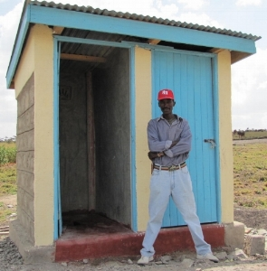 Mr. Kibet in front of the toilet he built for the school