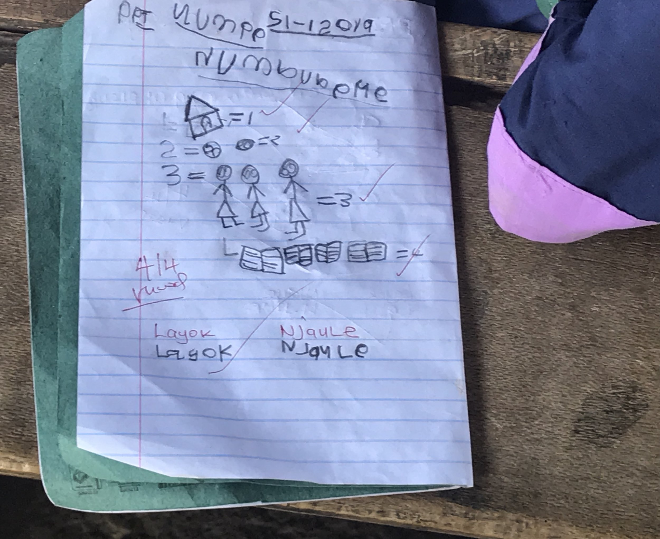 A nursery student learns to write numbers, count and write her name
