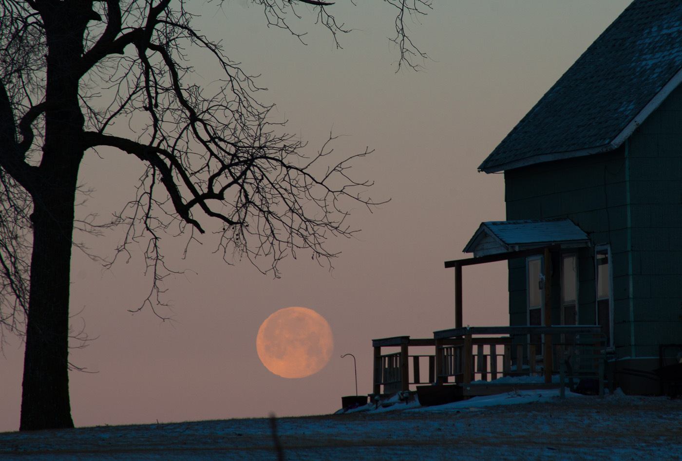 A full moon retires into the horizon as the sun rises on a winter day near Granger, Iowa.